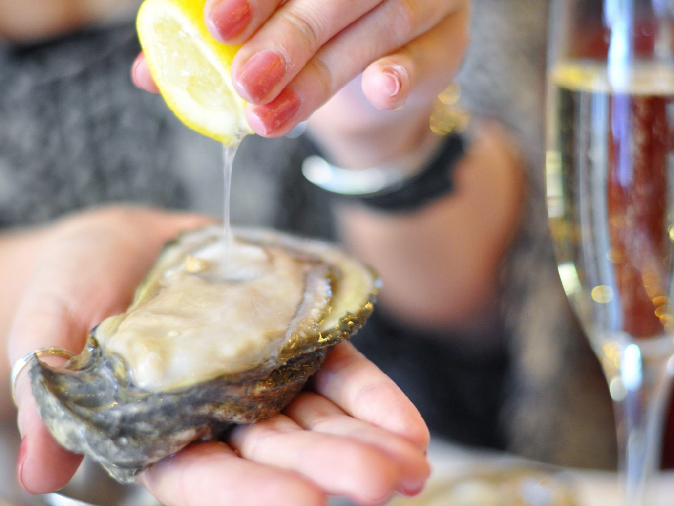 Food + Drink person oyster holding food hand clams oysters mussels and scallops Seafood animal source foods half mussel clam snack food eaten close