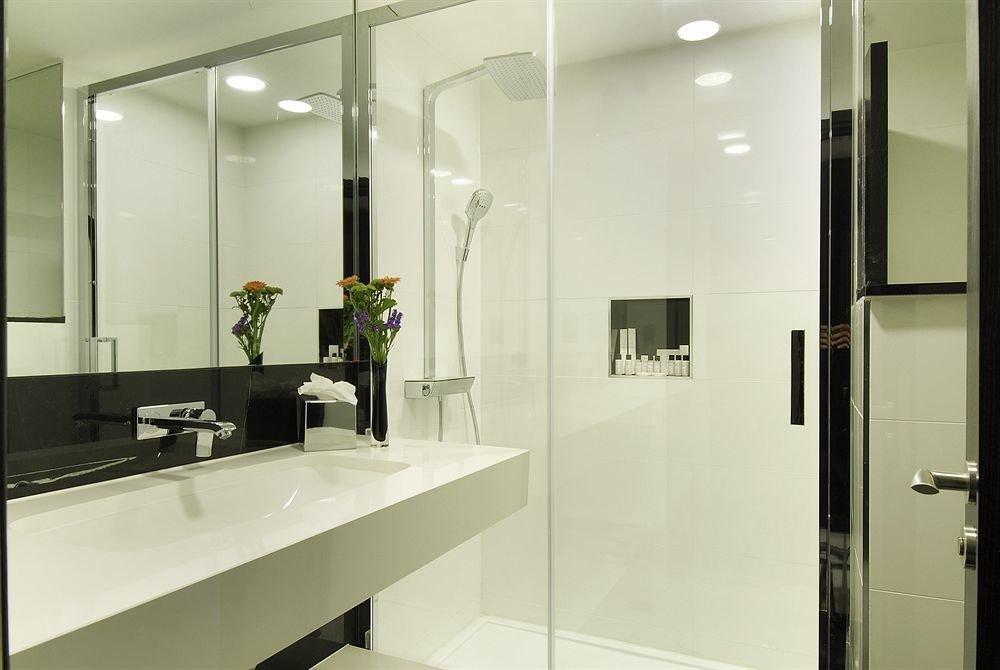bathroom mirror property lighting sink plumbing fixture toilet flooring stall