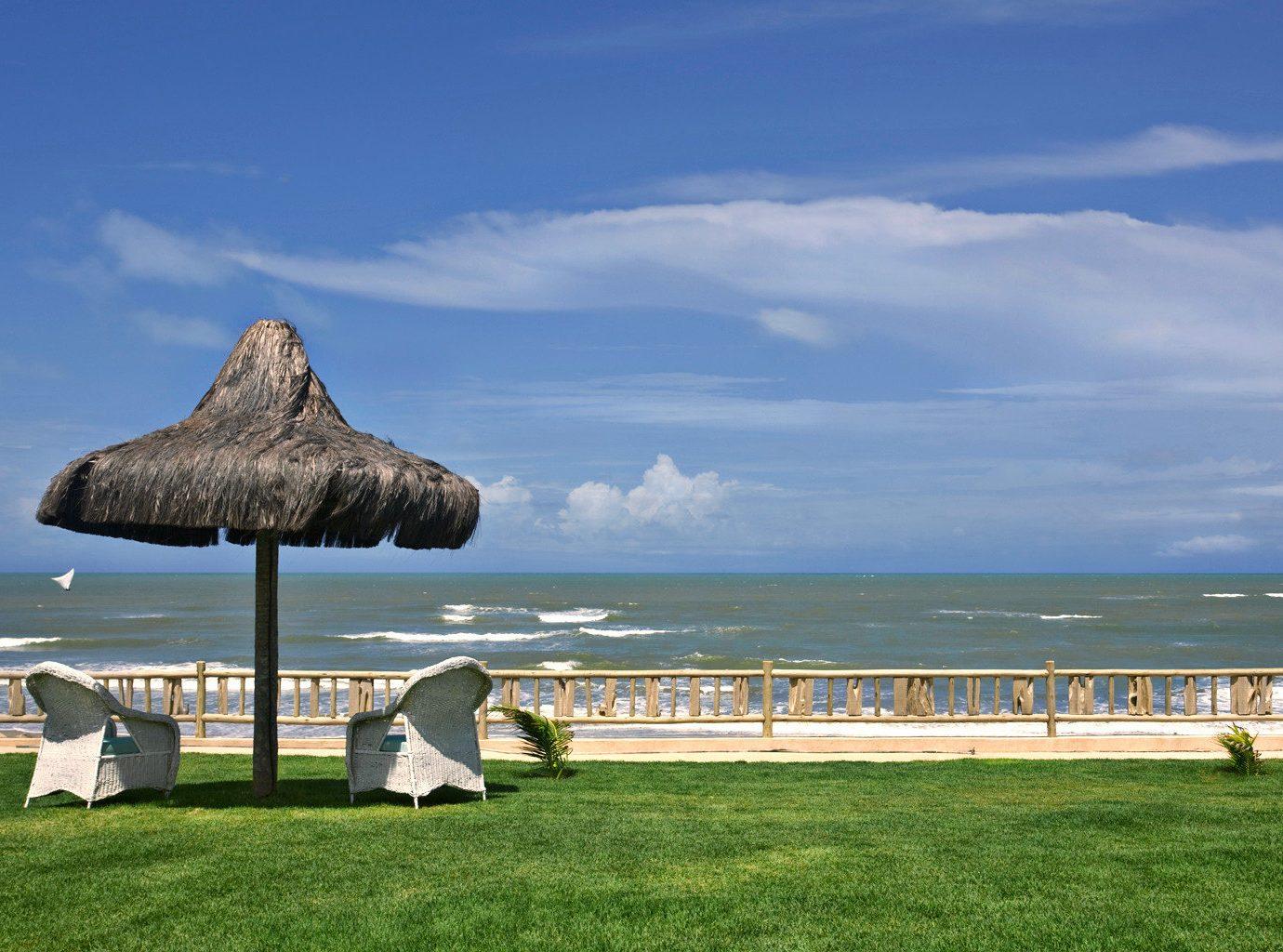 Beach Beachfront Grounds Outdoors Scenic views grass sky Sea shore Ocean horizon Coast cape Island lawn overlooking distance