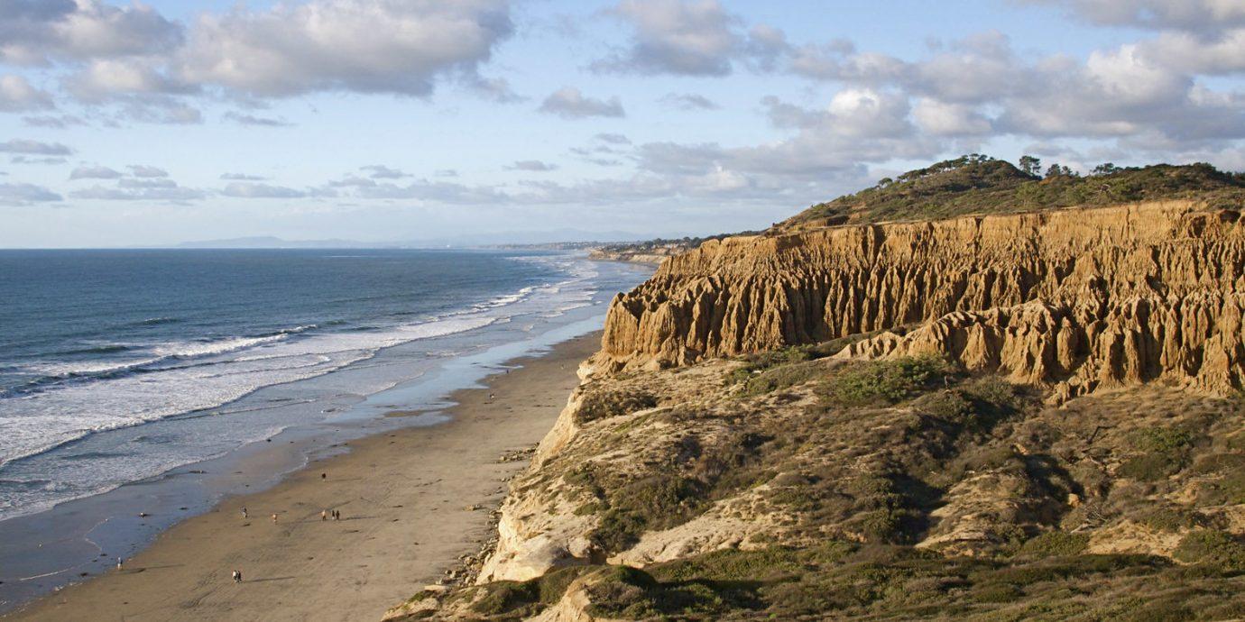 Beach Beachfront Ocean sky Nature water Coast cliff Sea rock shore terrain cape landscape sand geology formation wave material overlooking sandy