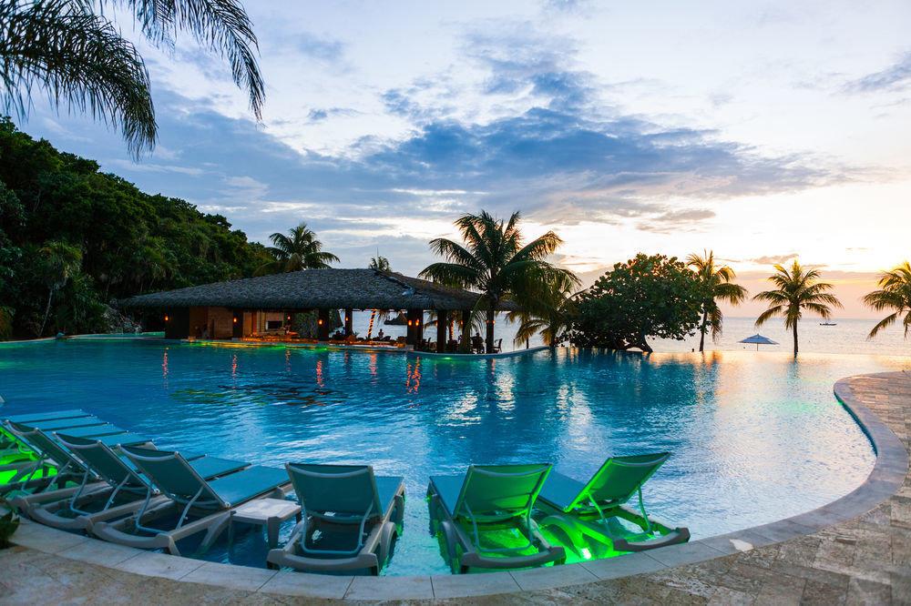 sky water tree Beach green swimming pool leisure Resort lined palm arecales caribbean resort town Lagoon tropics shore empty sandy