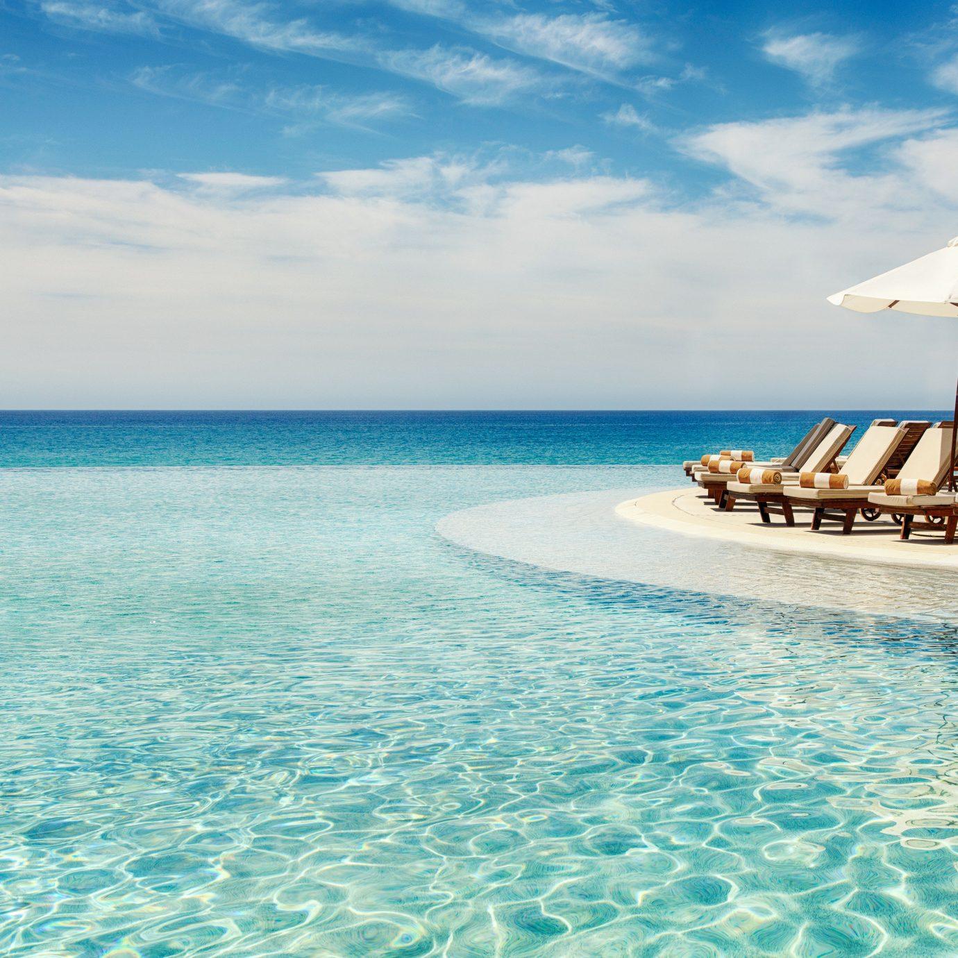 Beachfront Hotels Living Lounge Luxury Modern Pool Romance Tropical water sky outdoor umbrella chair Sea caribbean Ocean vacation horizon shore swimming pool Beach swimming blue Nature Lagoon Resort Island Coast atoll bay islet cay cape day