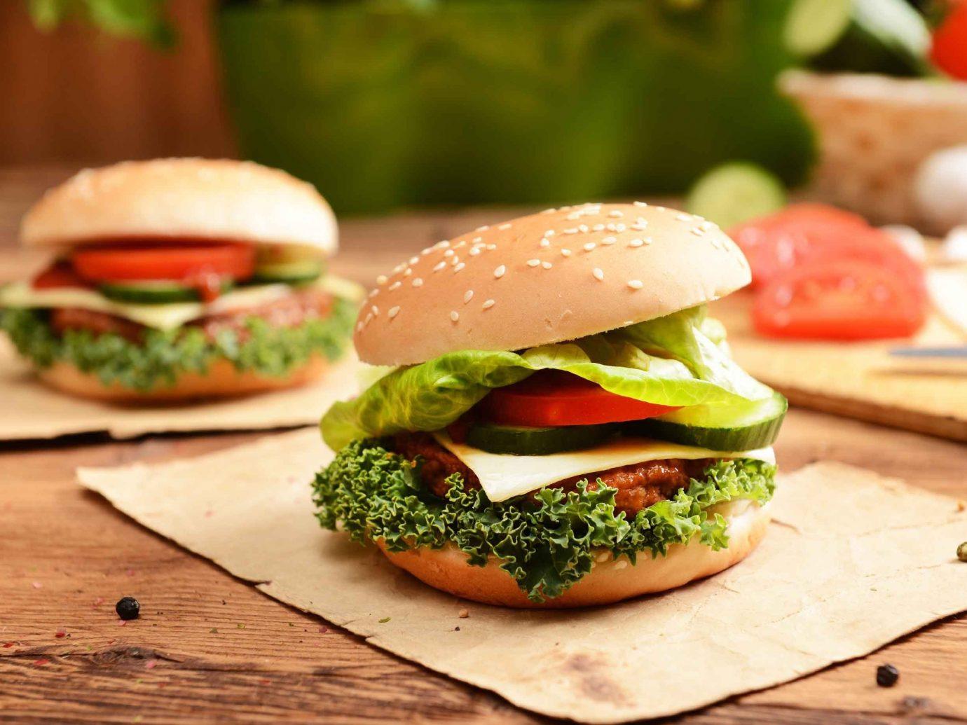 Food + Drink table food board hamburger wooden dish veggie burger produce sandwich slice vegetable meat cheeseburger blt meal fast food sliced