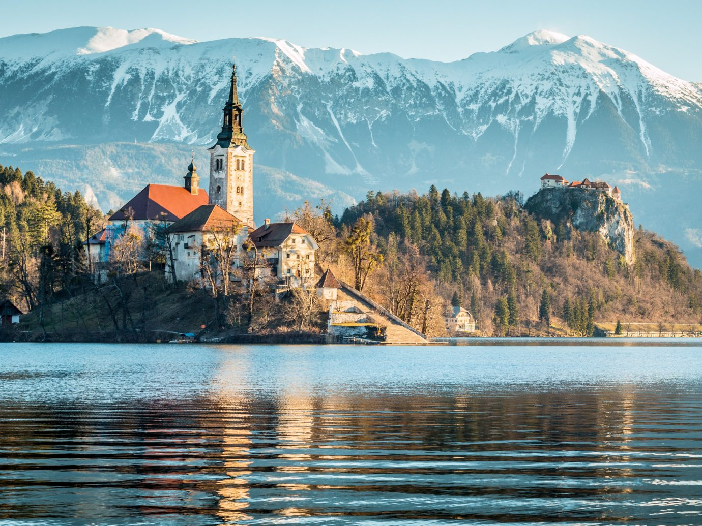 Mountains + Skiing Trip Ideas mountain outdoor water sky reflection Nature Lake mountainous landforms mountain range background morning mount scenery alps tree Sea landscape Winter tourism Coast fjord loch cloud fell surrounded shore distance