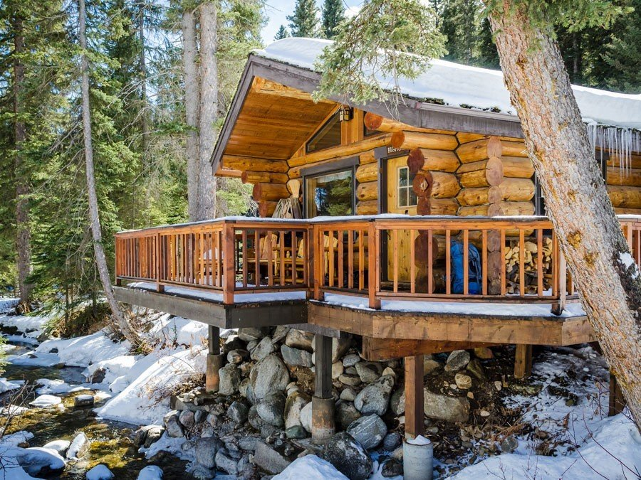 Hotels tree outdoor snow log cabin hut home wood outdoor structure cottage shack backyard house area surrounded