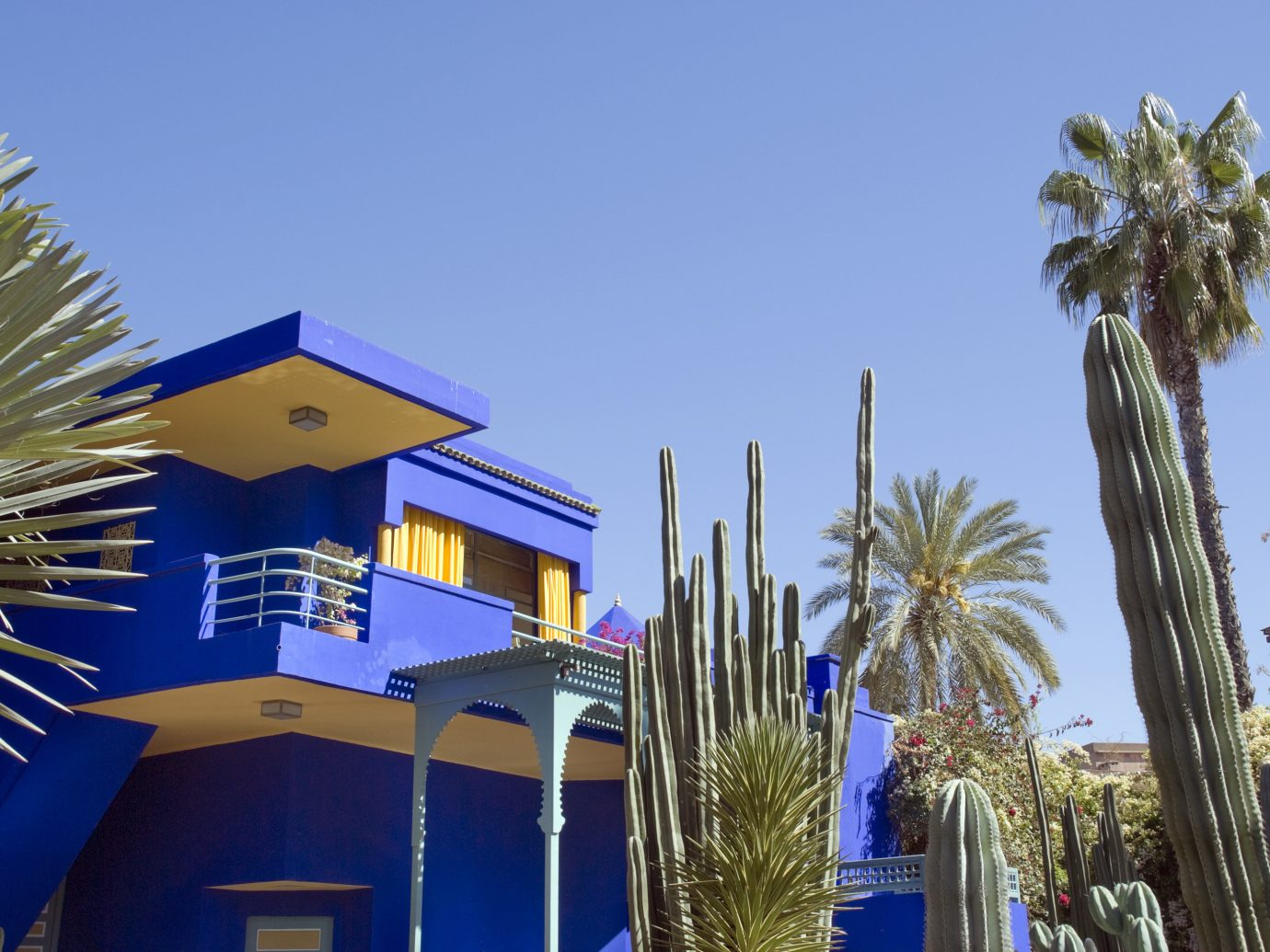 Trip Ideas sky tree outdoor blue majorelle blue property palm tree arecales plant palm Architecture home real estate building daytime house residential area neighbourhood City facade vacation lined