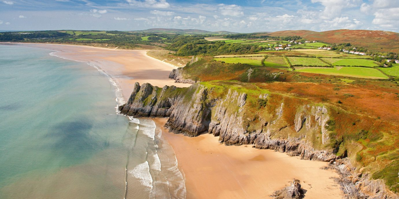 Jetsetter Guides sky outdoor Nature grass body of water landform shore Coast geographical feature water Sea Beach vacation Ocean reflection landscape aerial photography bay cliff wave terrain reservoir cape cove land