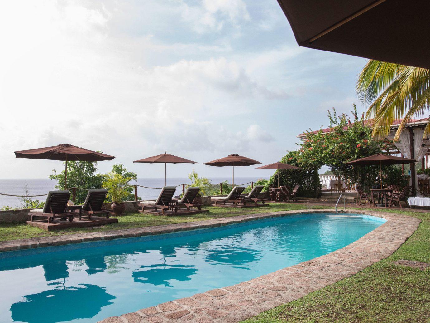 Hotels outdoor sky umbrella grass water Resort swimming pool Pool property leisure estate vacation lawn Villa real estate condominium swimming bay caribbean blue day