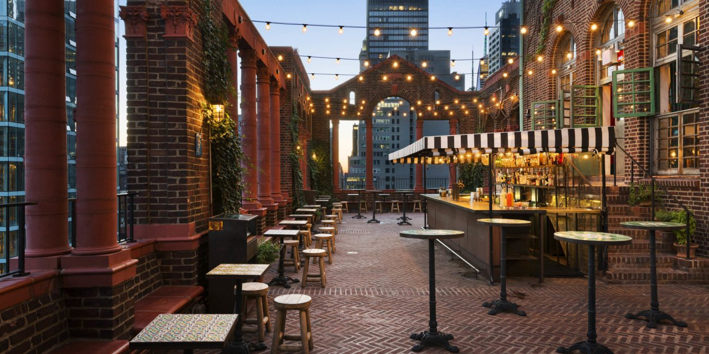 artistic artsy Bar bar seating Boutique brick wall City city lights city views Hip Hotels industrial lights Luxury night lights outdoor bar outdoor lounge Patio Rooftop string lights Terrace trendy Trip Ideas urban view outdoor plaza neighbourhood Downtown restaurant outdoor structure
