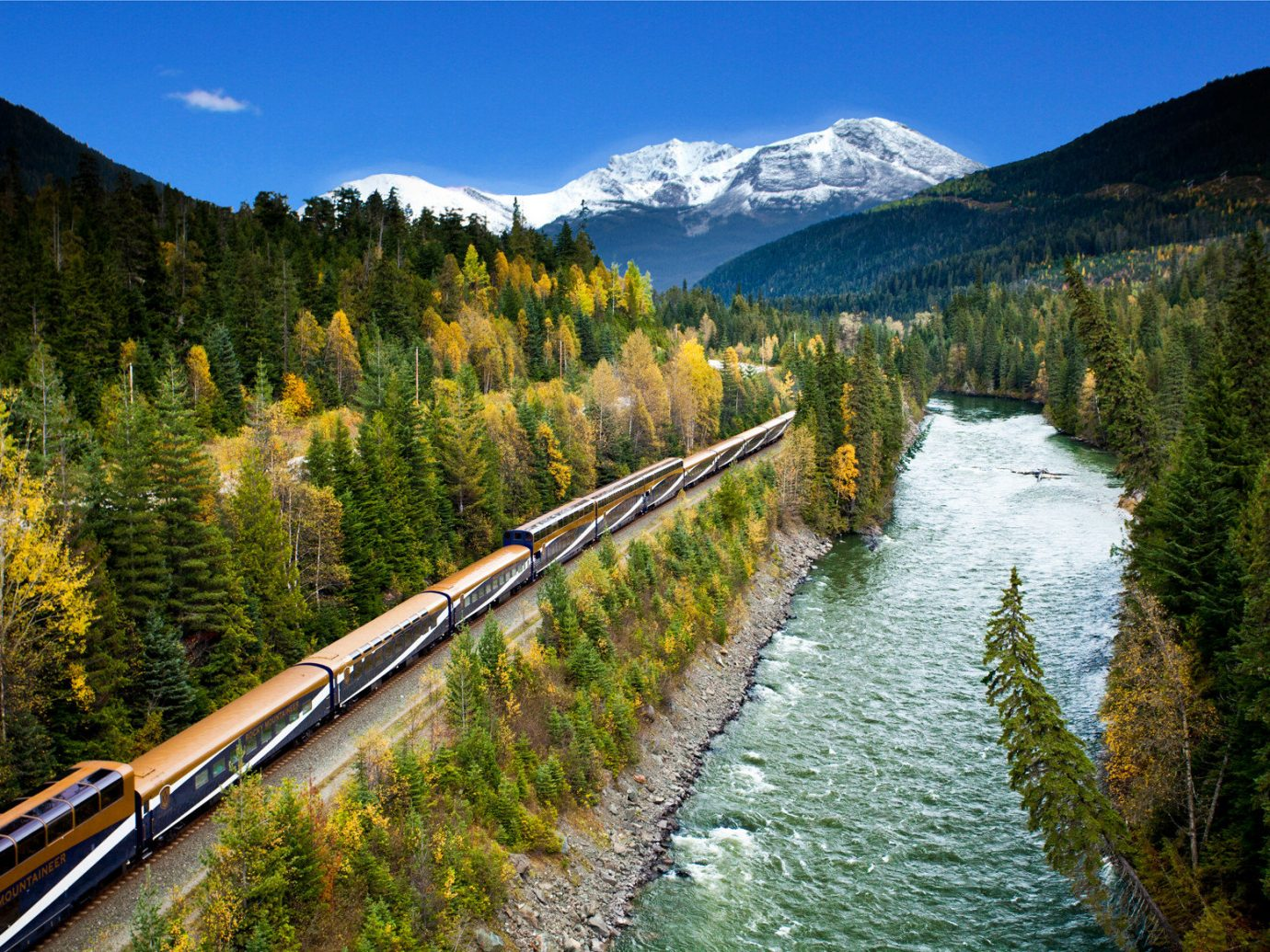 Hotels National Parks Outdoors + Adventure Trip Ideas tree train outdoor sky mountain track grass mountainous landforms landform geographical feature transport wilderness mountain range River Nature Forest traveling reflection valley Lake mountain pass landscape waterway autumn reservoir alps surrounded hillside long wooded lush wood moving highland