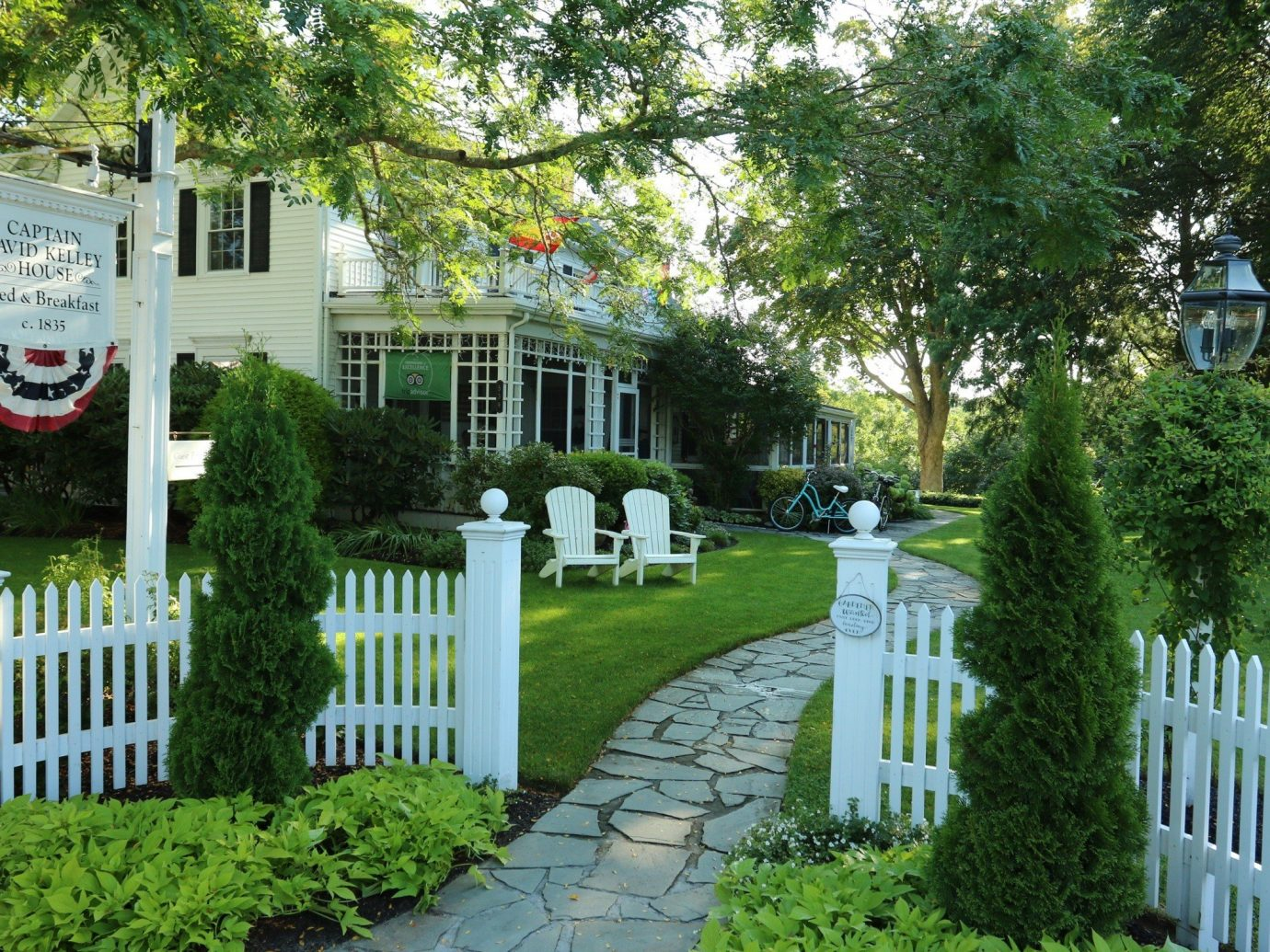Hotels tree outdoor grass Fence neighbourhood property home house Garden building walkway picket fence park yard outdoor structure estate residential area backyard real estate plant cottage landscaping mansion home fencing white shrub Courtyard lawn landscape plantation porch surrounded