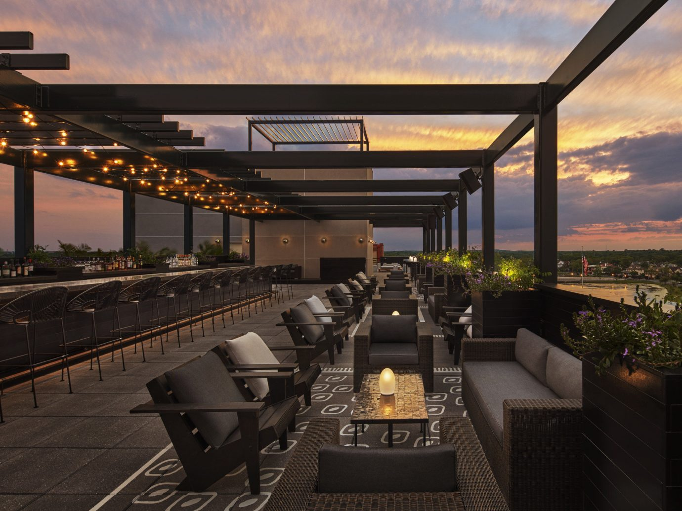 ambient lighting bar seating calm dawn dusk Elegant golden hour Hotels lights lounge chairs Luxury majestic night lights orange sky outdoor lounge regal remote Rooftop serene Solo Travel sophisticated Sunset view sky outdoor bridge lighting evening estate interior design