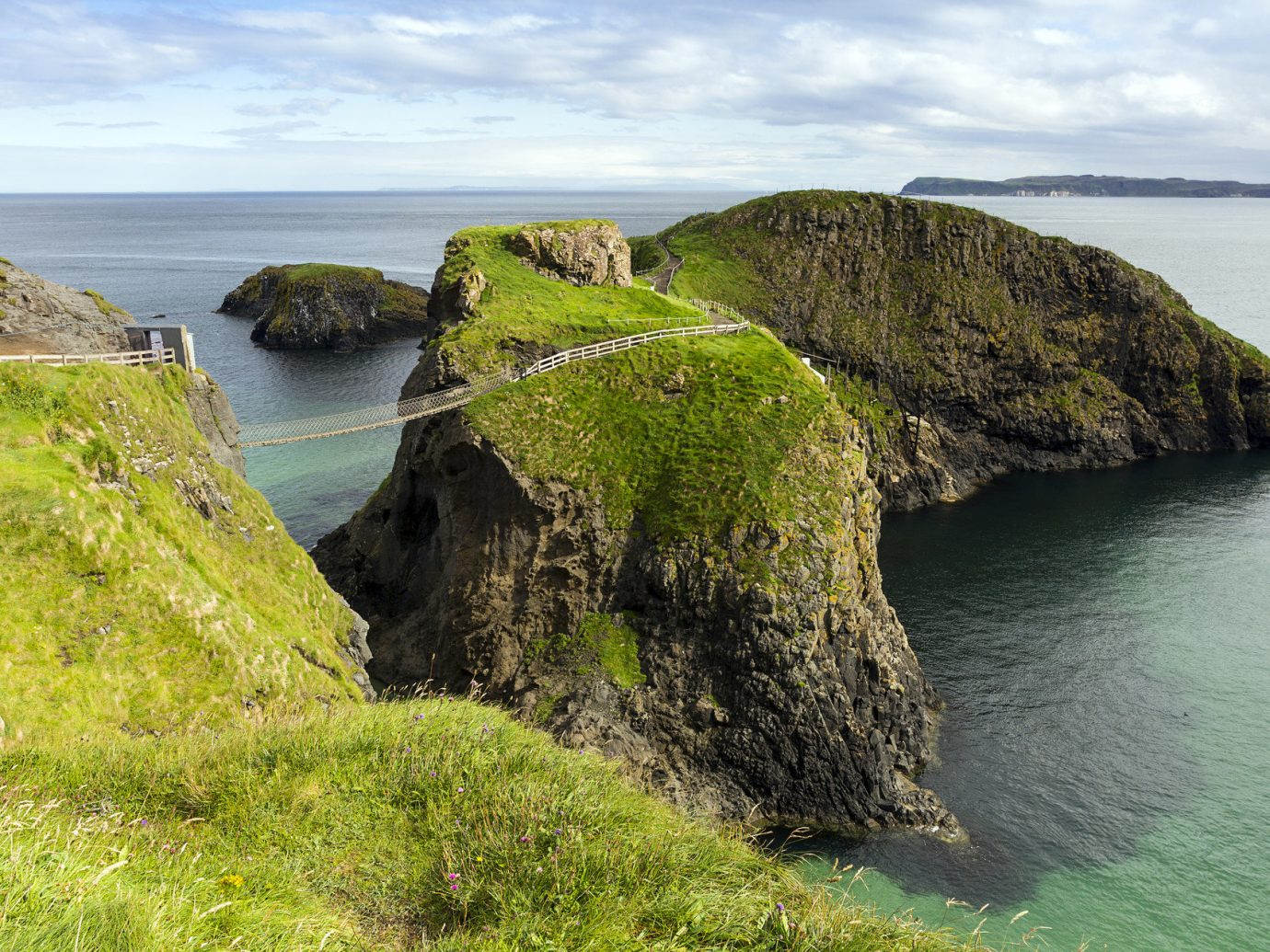 Carrick-a-Rede Rope Bridge Offbeat outdoor water sky grass Coast cliff rock Nature shore Sea landform geographical feature mountain body of water Ocean green terrain rocky bay islet Beach cove hill bridge cape Island landscape waterway stack hillside overlooking lush