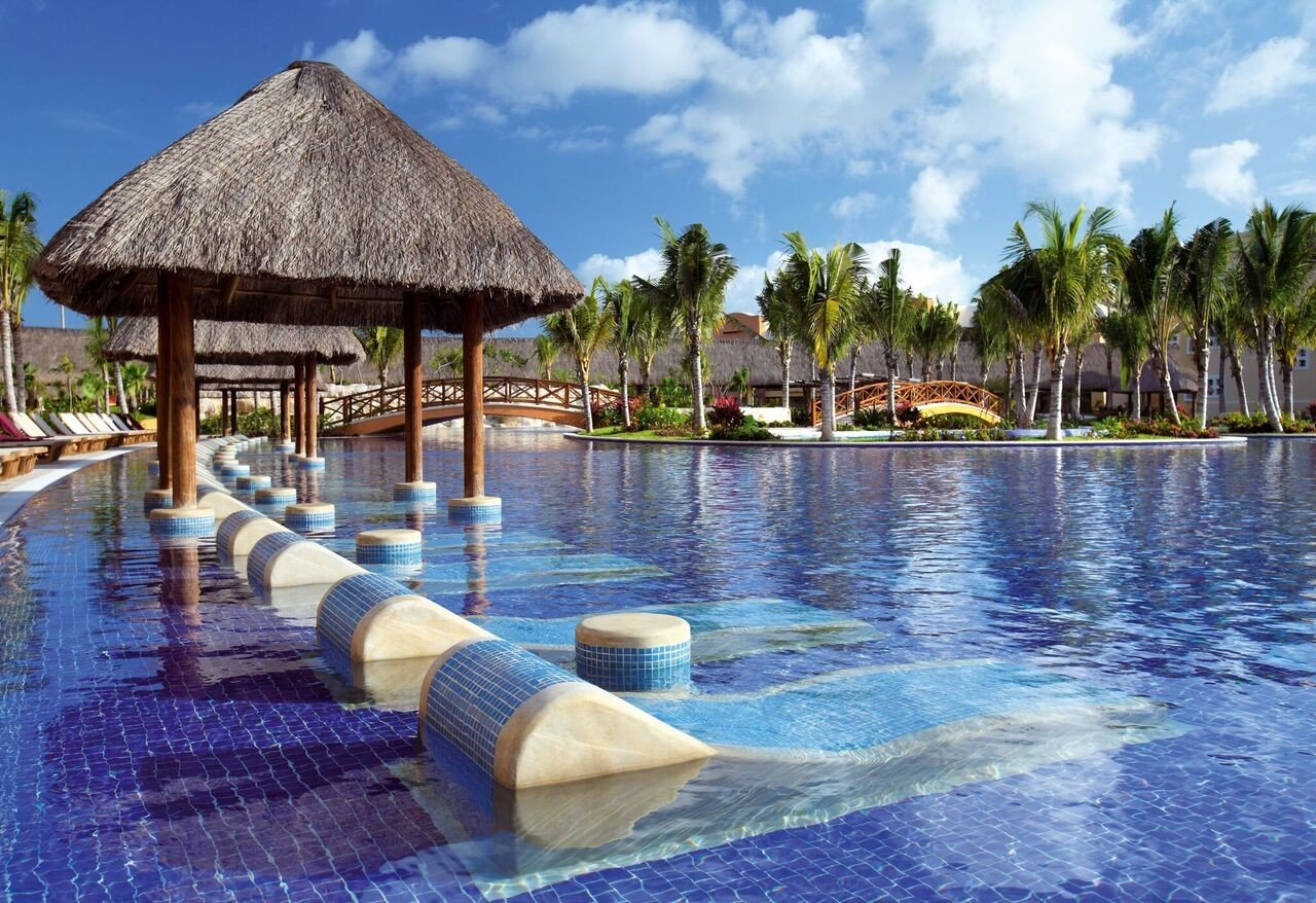 All-Inclusive Resorts Family Travel Hotels water outdoor sky Resort swimming pool leisure resort town caribbean vacation tropics tourism palm tree Lagoon arecales real estate Pool Sea estate several swimming day surrounded