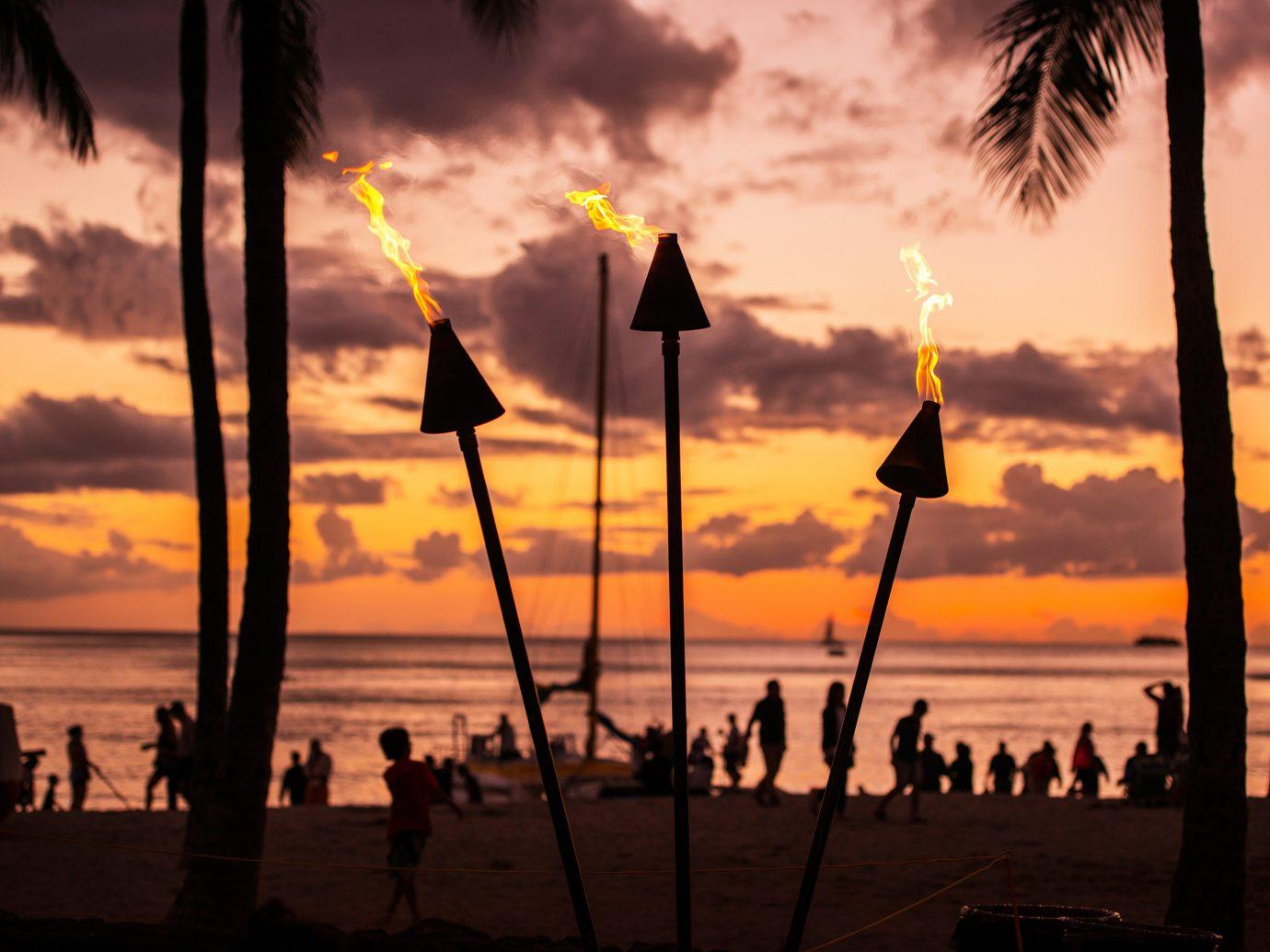 Beach Jetsetter Guides Ocean Scenic views Sunset sky outdoor water cloud Sun evening dusk morning afterglow dawn sunlight sunrise Sea silhouette tree setting clouds sailing vessel shore sandy