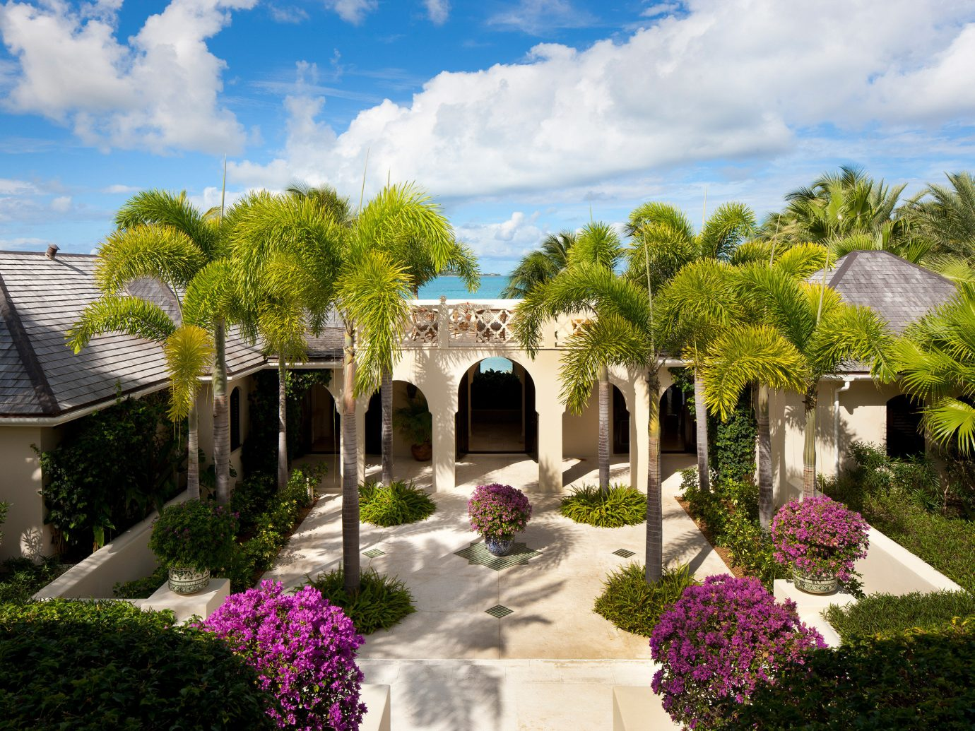 All-inclusive Beach Beachfront Courtyard Exterior Garden Grounds Hotels Island Luxury Resort Trip Ideas Waterfront tree sky outdoor flower property estate flora house home vacation mansion Villa real estate hacienda backyard plant yard lawn Village surrounded stone