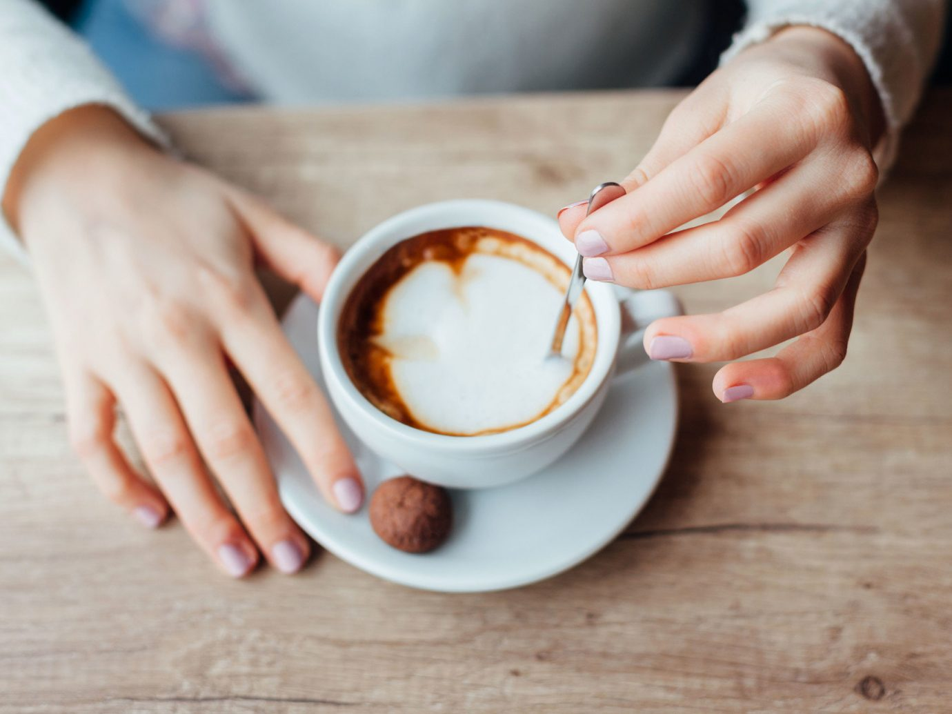 Girl stirring a cup of coffee.