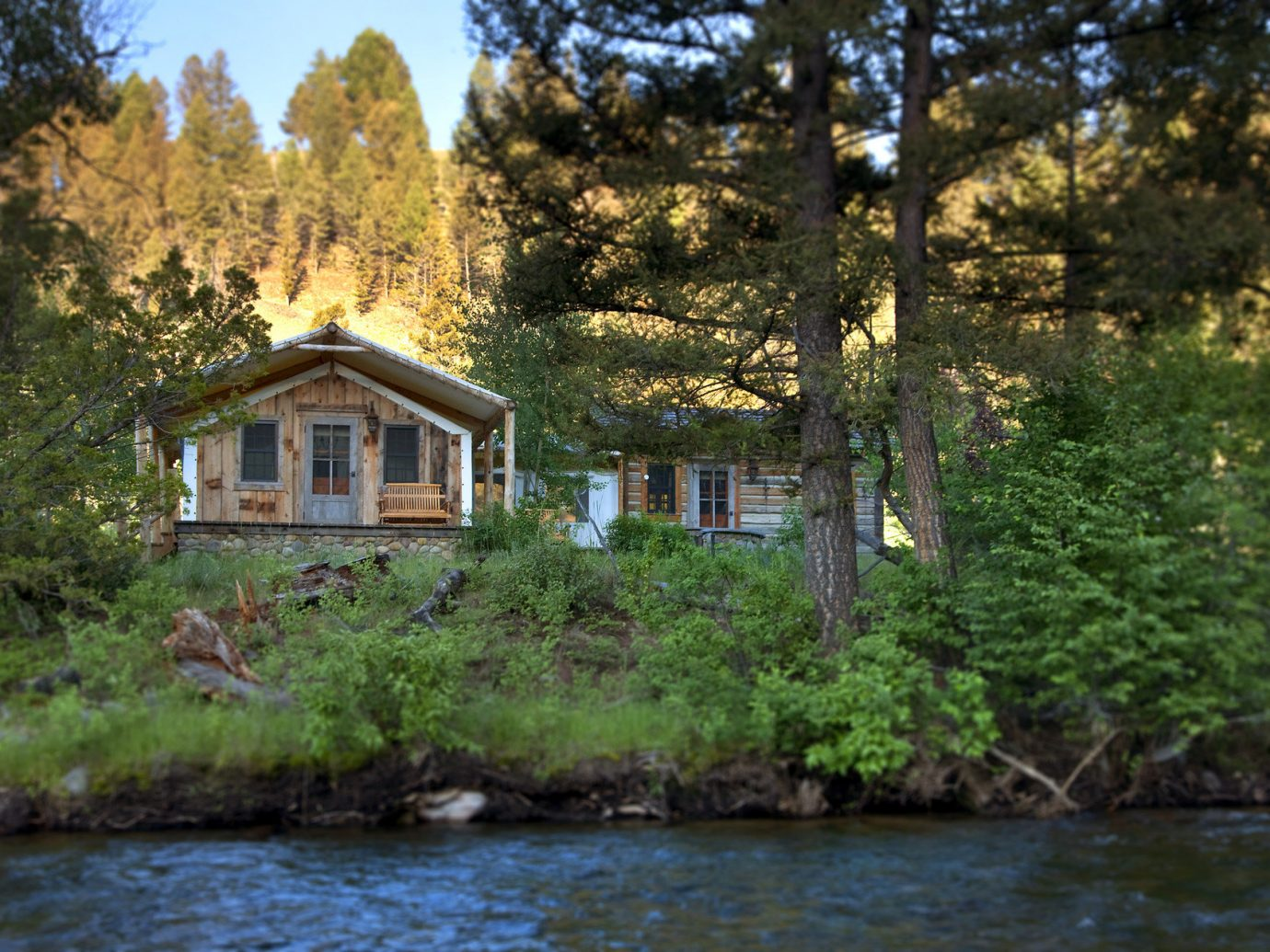 Glamping Hotels Luxury Travel Montana Outdoors + Adventure Trip Ideas tree outdoor water River house estate Lake waterway woodland cottage autumn pond surrounded Forest wooded