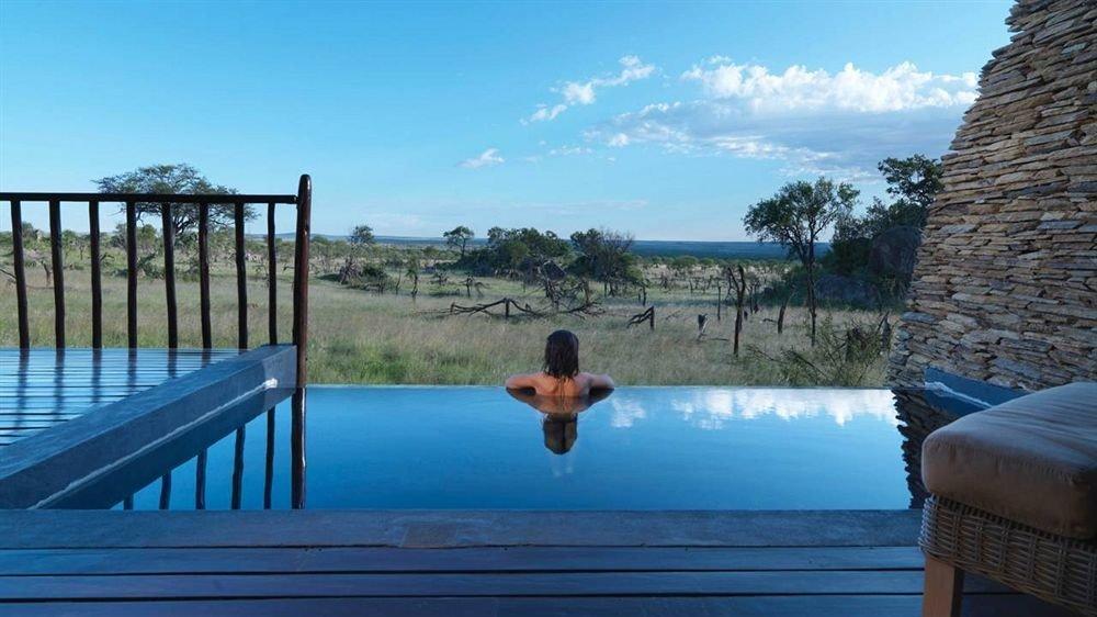 Women In Beautiful Infinity Pool Overlooking Grassland And Ocean