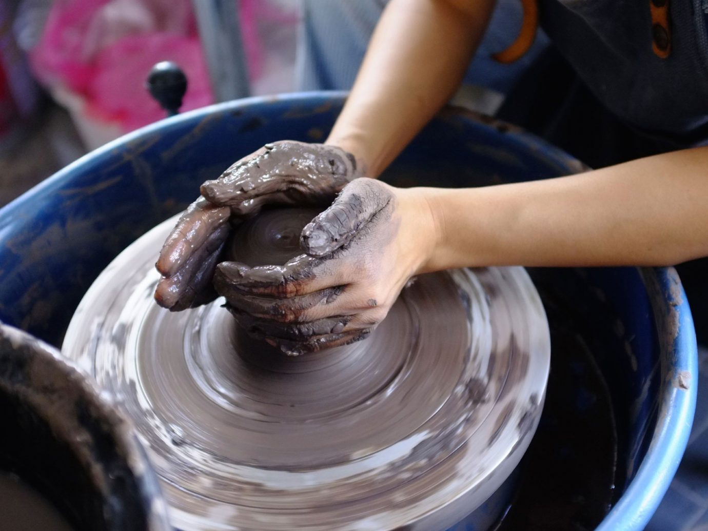 Person throwing clay on a wheel