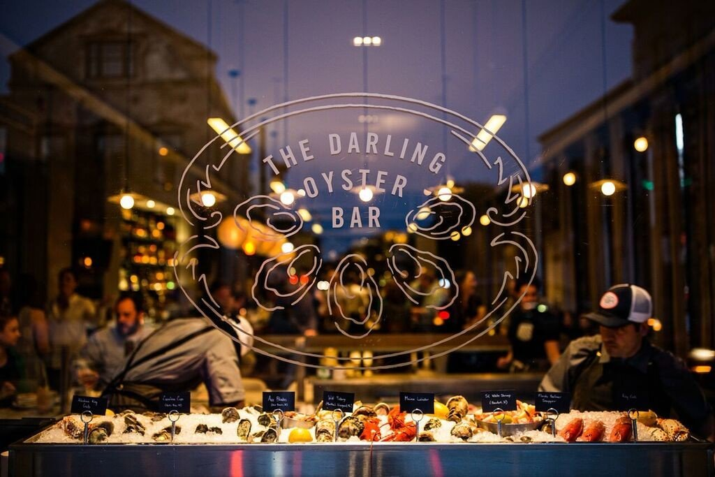 ambient lighting crowd Dining Exterior food Food + Drink interior oysters people reflection restaurant sign window person night meal device