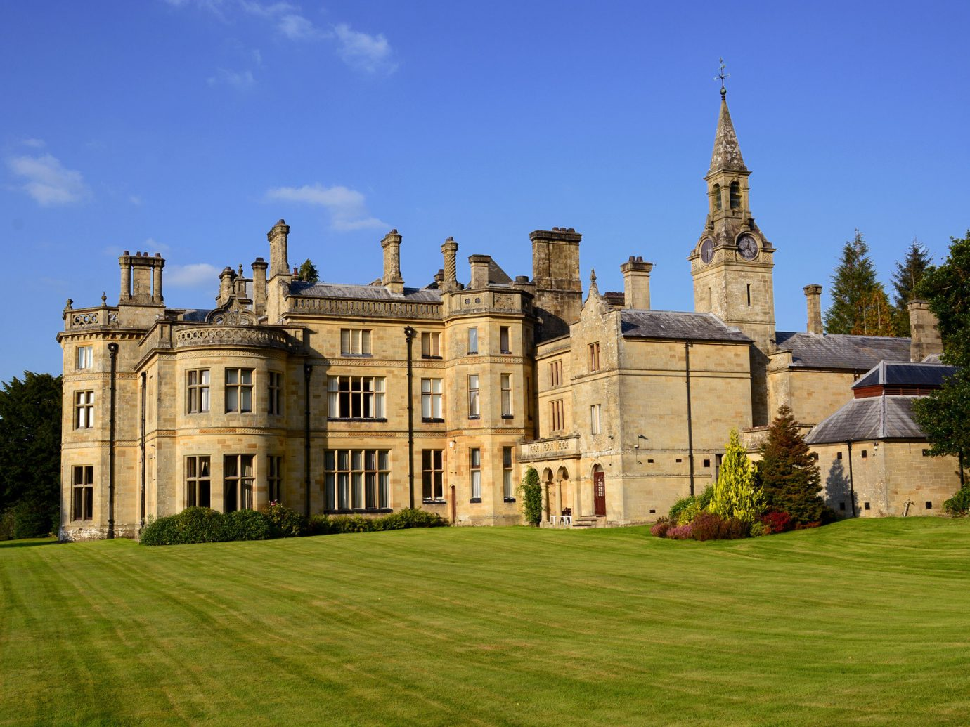 Trip Ideas grass sky outdoor building château stately home estate landmark house Architecture palace castle mansion manor house grassy monastery facade place of worship abbey old stone lush