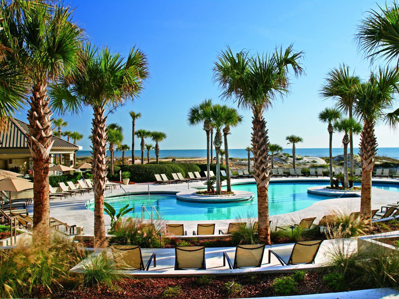 Hotels tree outdoor palm sky plant Pool swimming pool Resort property leisure estate vacation arecales resort town real estate Lagoon Villa lawn lined area furniture Garden shade colorful