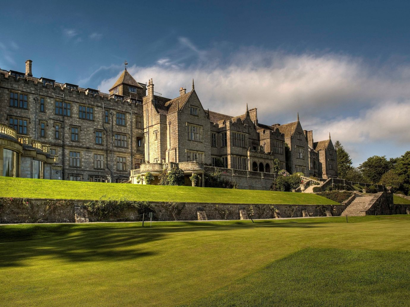 Hotels grass outdoor sky building château stately home castle estate rural area lawn old palace abbey mansion monastery grassy stone day lush