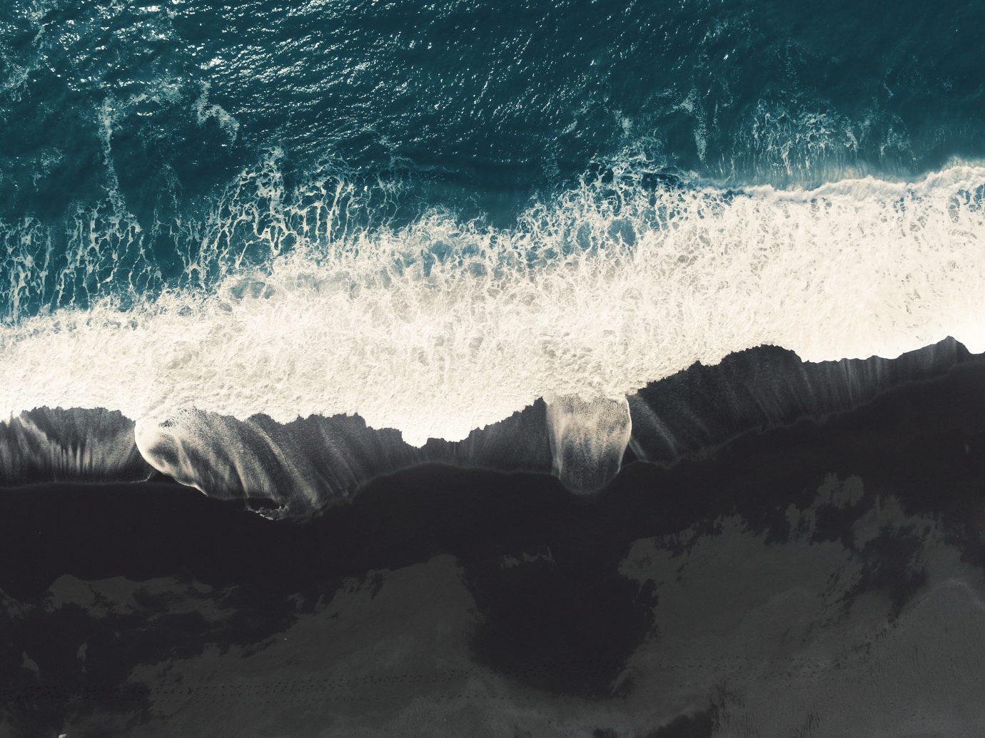 Iceland Offbeat Outdoors + Adventure outdoor water sport wave atmospheric phenomenon wind wave water Ocean weather Sea geological phenomenon horizon surfing cloud reflection sunlight Coast terrain wind snow