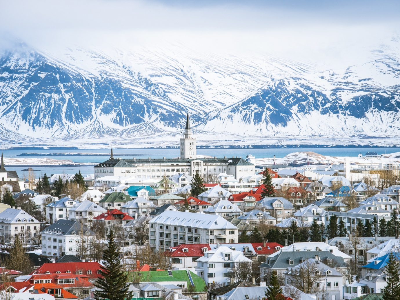 Boutique Hotels Hotels Iceland Reykjavík Winter snow mountain range Town mountain sky alps City glacial landform tourist attraction tourism arctic tree mountain village water mount scenery Village landscape Lake fell freezing house