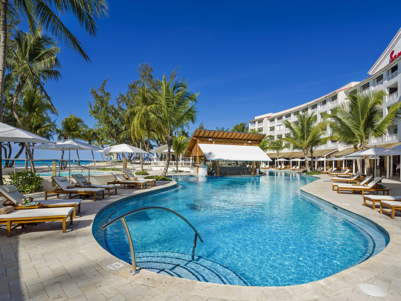 All-Inclusive Resorts Hotels outdoor tree sky Resort swimming pool leisure resort town building palm tree arecales vacation real estate hotel estate caribbean tropics tourism Villa bay Lagoon water blue palm lined