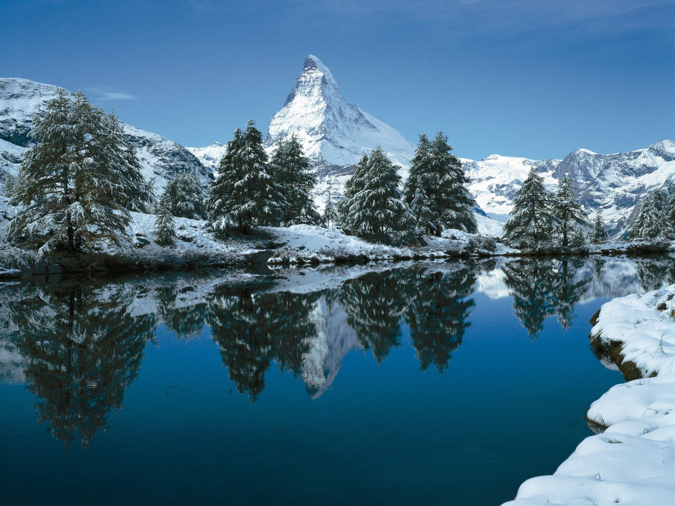 alpine skiing Mountains + Skiing Trip Ideas tree outdoor sky mountainous landforms snow Nature mountain reflection landform wilderness mountain range Winter Lake weather season cloud landscape alps ice Forest surrounded hillside