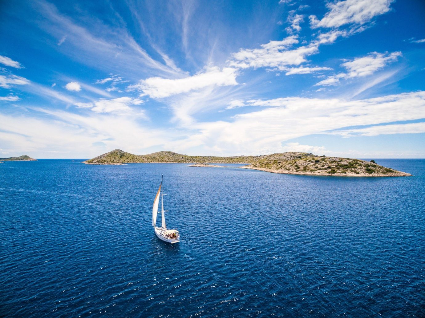 Cruise Travel Trip Ideas water sky outdoor Sea Lake horizon blue Boat Ocean body of water shore cloud Coast Beach vacation Nature sunlight reflection bay wave cape Island islet caribbean sailing vessel distance day