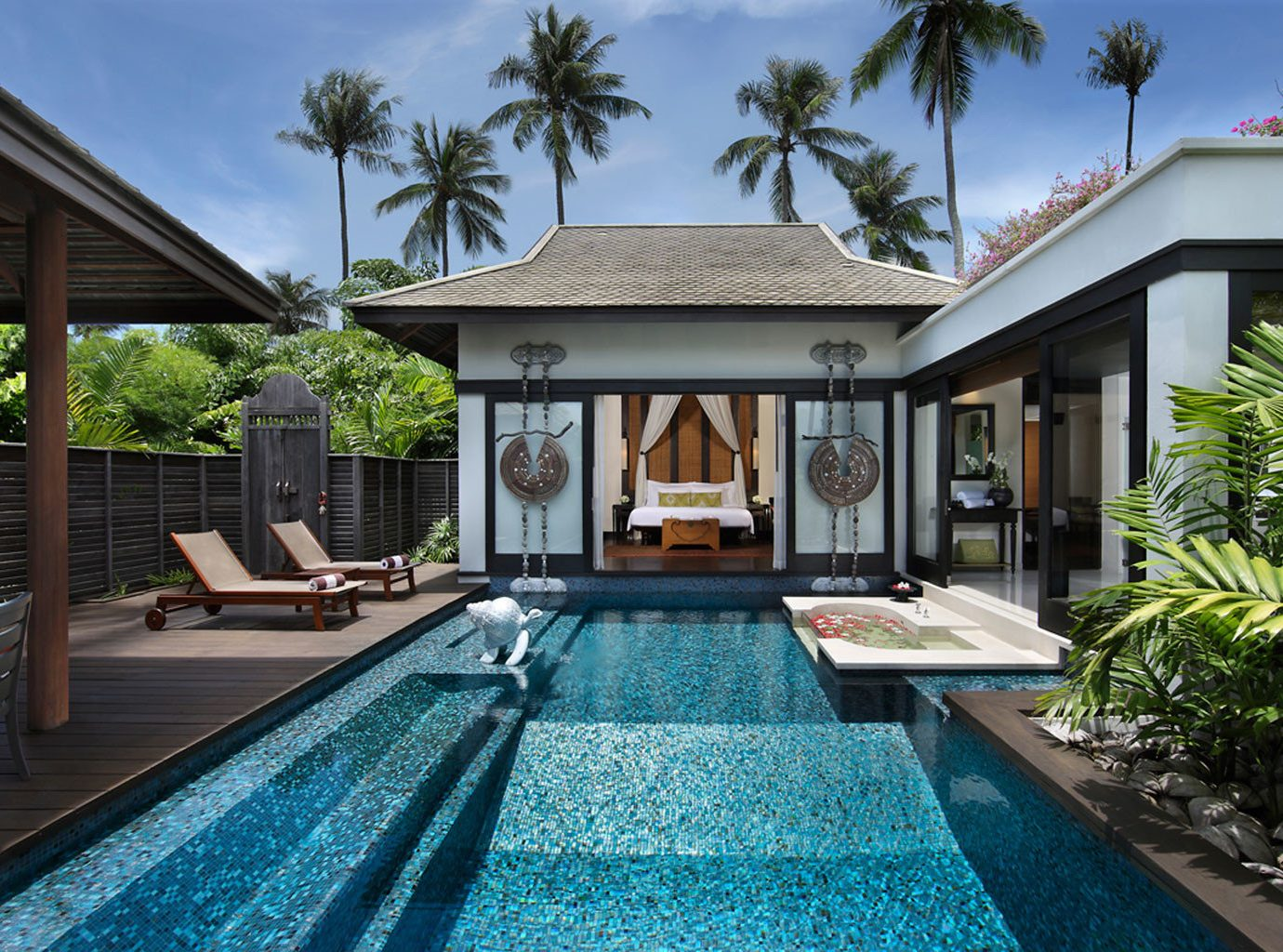 Hotels outdoor sky tree swimming pool building property estate Resort house home backyard Villa real estate condominium mansion cottage outdoor structure palm Garden stone walkway