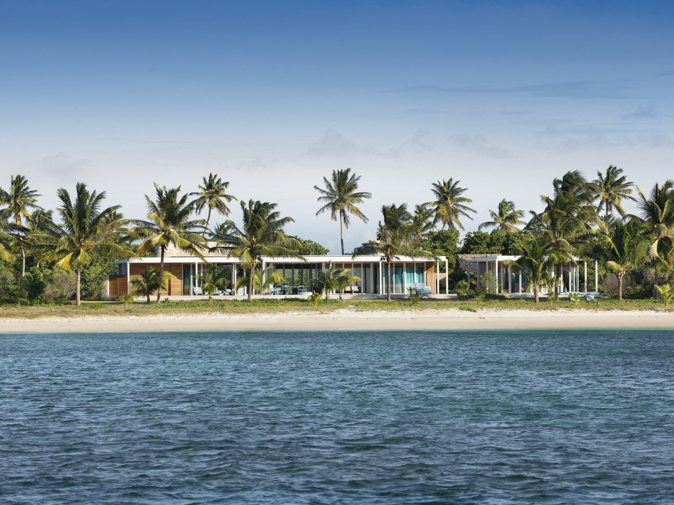 All-Inclusive Resorts Hotels sky water outdoor body of water Sea coastal and oceanic landforms palm tree arecales shore Ocean tropics tree Resort real estate Coast Beach daytime vacation bay Island caribbean Lagoon horizon tourism palm plant cloud house day sandy