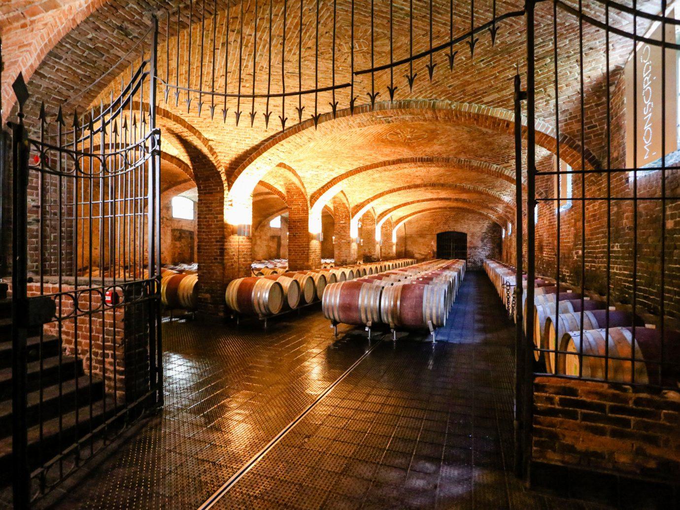 Food + Drink Hotels Italy Luxury Travel Trip Ideas indoor building floor room Winery arch wine cellar night basement area gate