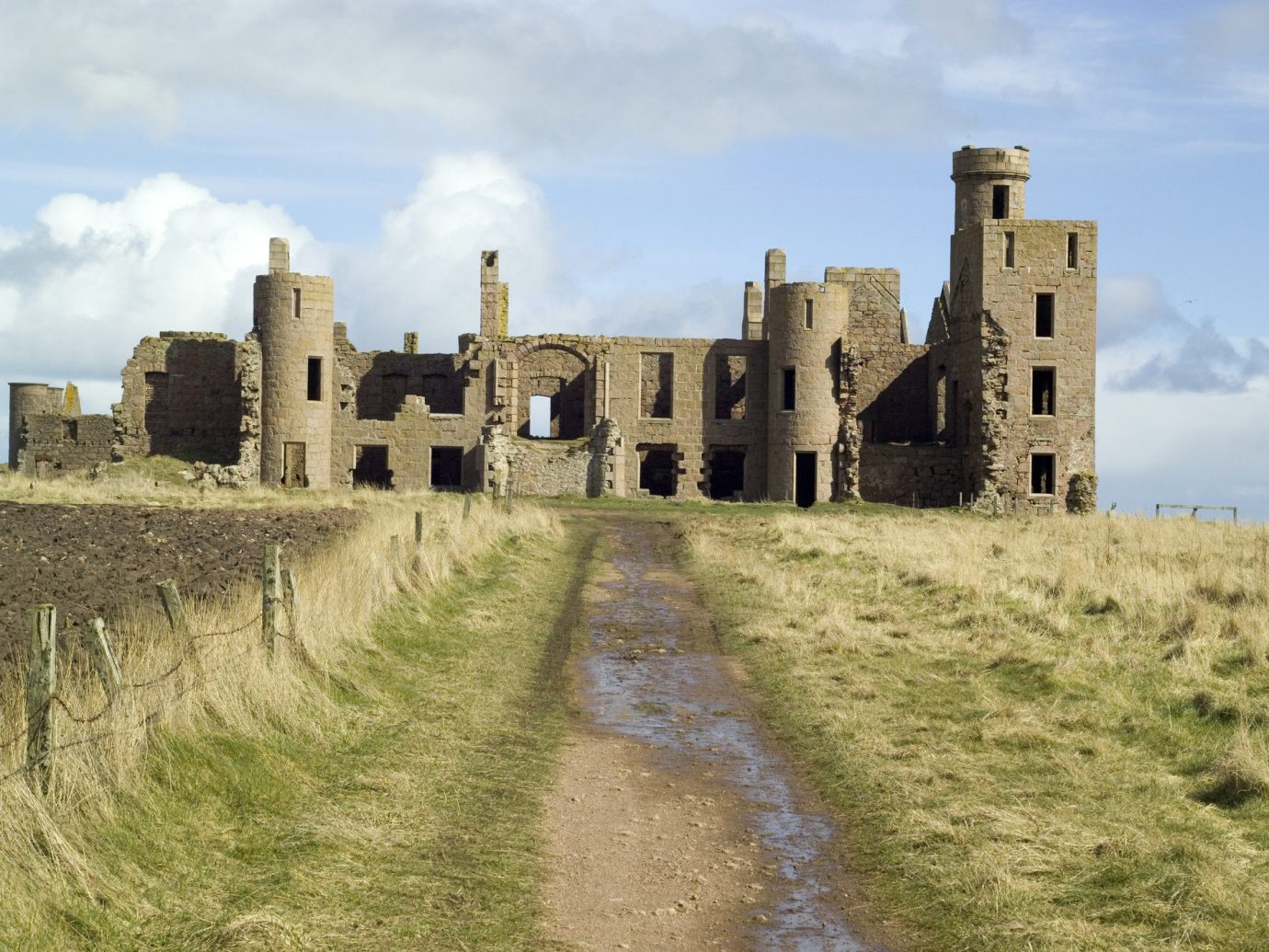 Arts + Culture Offbeat grass sky outdoor building castle medieval architecture Ruins historic site history Village fortification estate château ancient history stone dirt