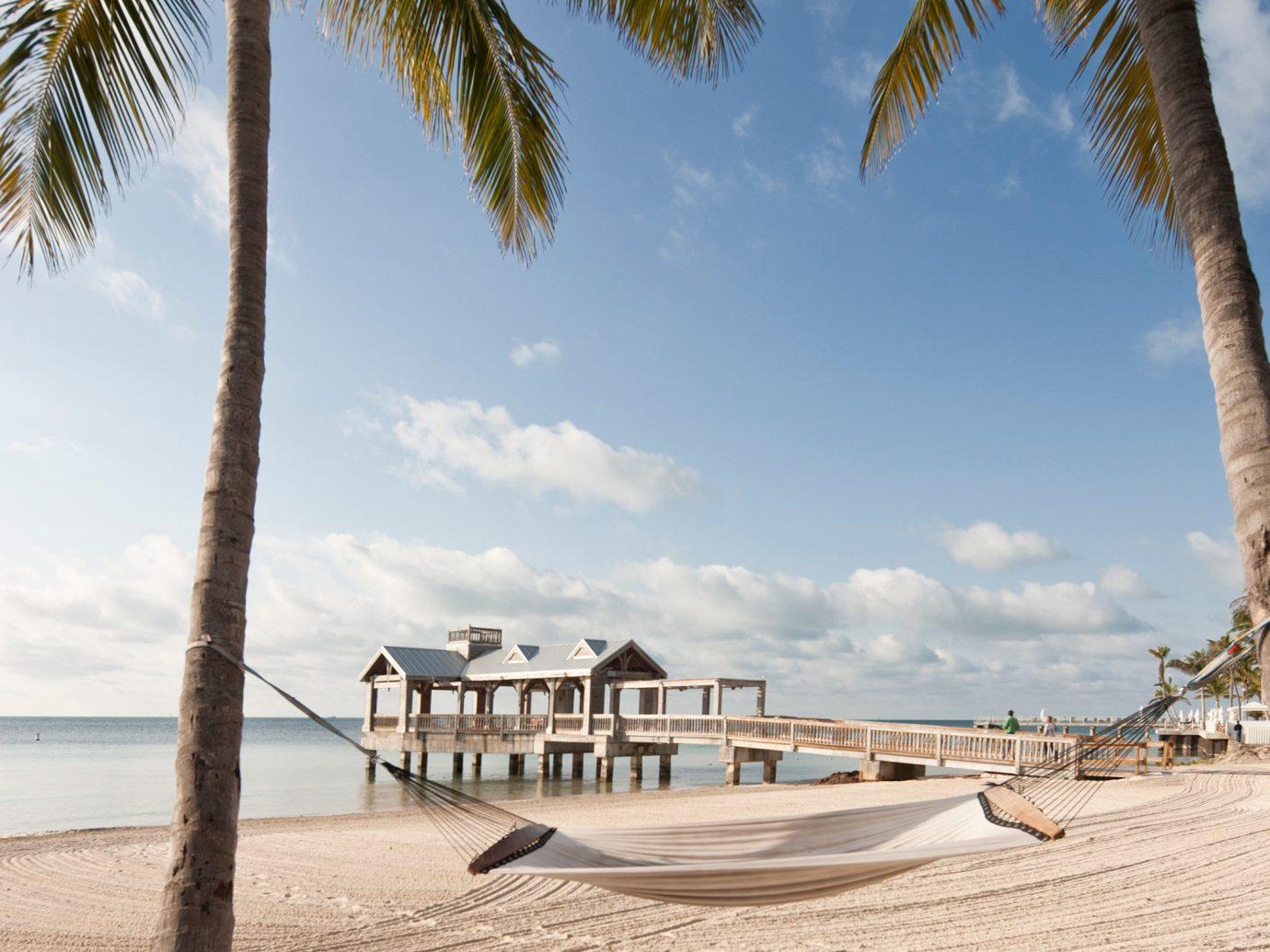 Beach Hotels Ocean sky outdoor tree ground shore body of water Sea plant palm vacation Coast arecales sand caribbean bay palm family Resort sandy sunny shade day
