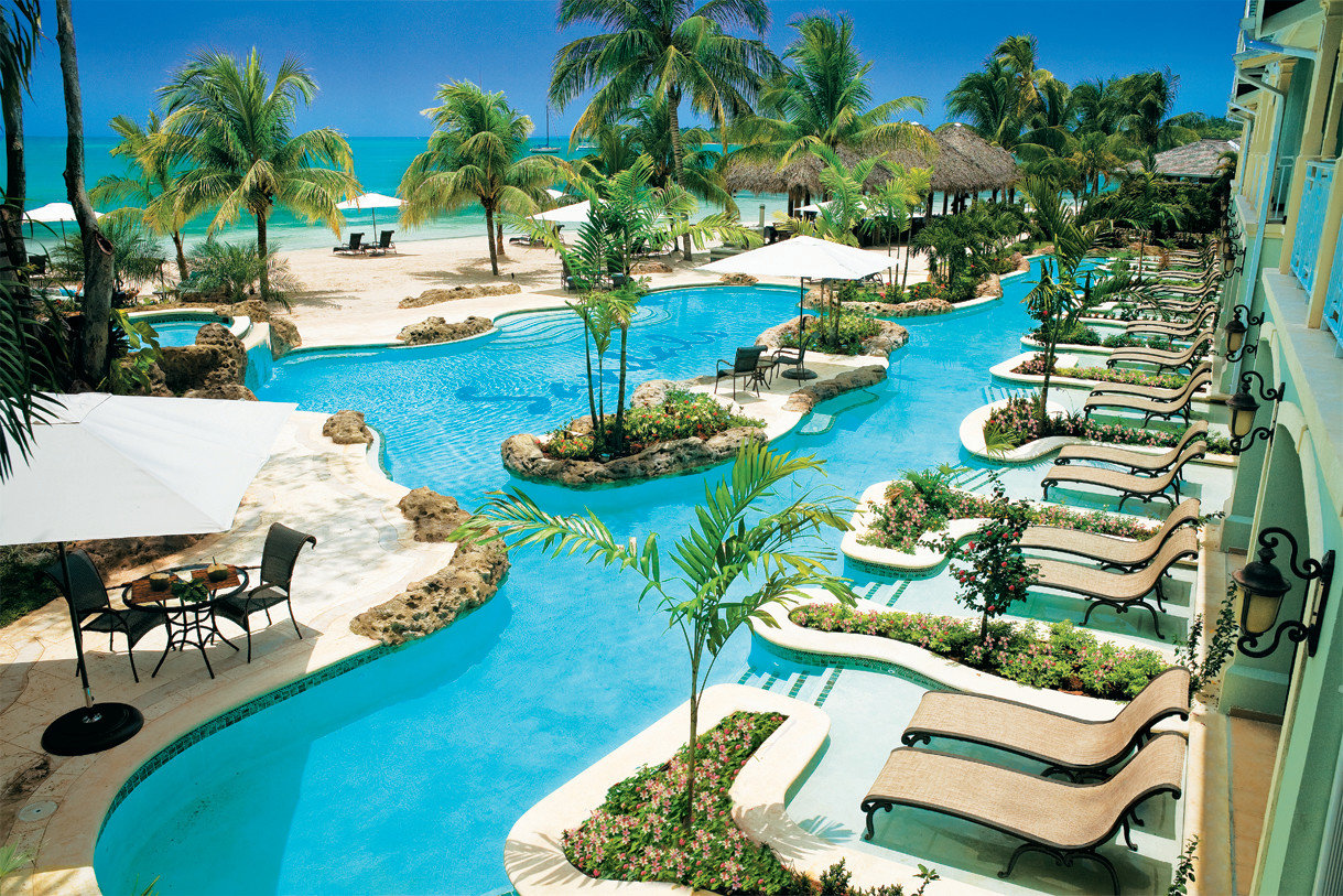 Hotels tree outdoor Resort chair Water park amusement park leisure Pool swimming pool vacation park lawn outdoor recreation estate resort town caribbean recreation lined furniture palm Garden decorated Deck colorful several