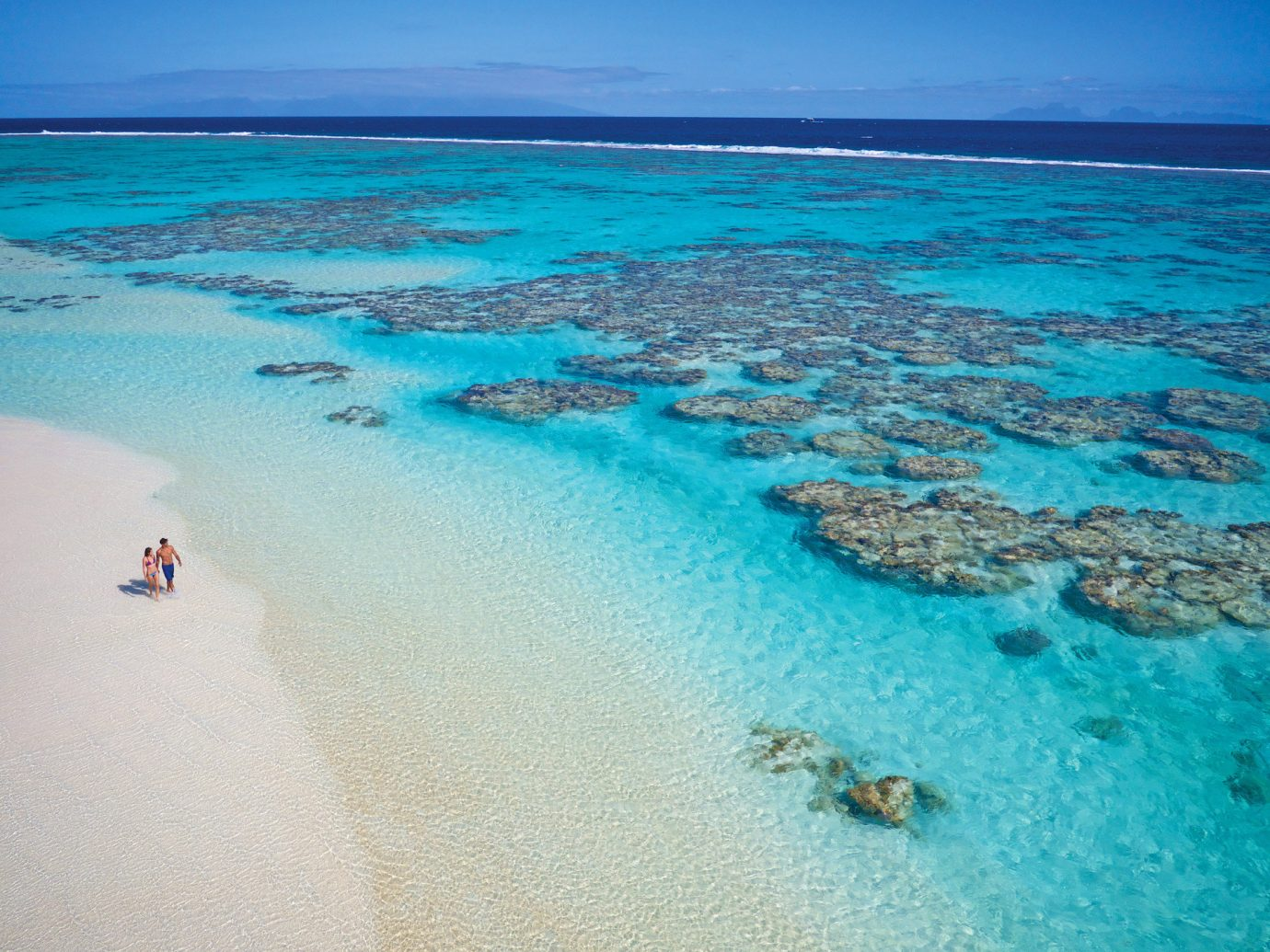 Beach clear water isolation Ocean Offbeat people remote serene Tropical turquoise walking white sands water sky outdoor Sea landform geographical feature body of water Nature shore Pool swimming Coast wind wave blue sand caribbean Lagoon wave cape reef Island bay islet sandy day