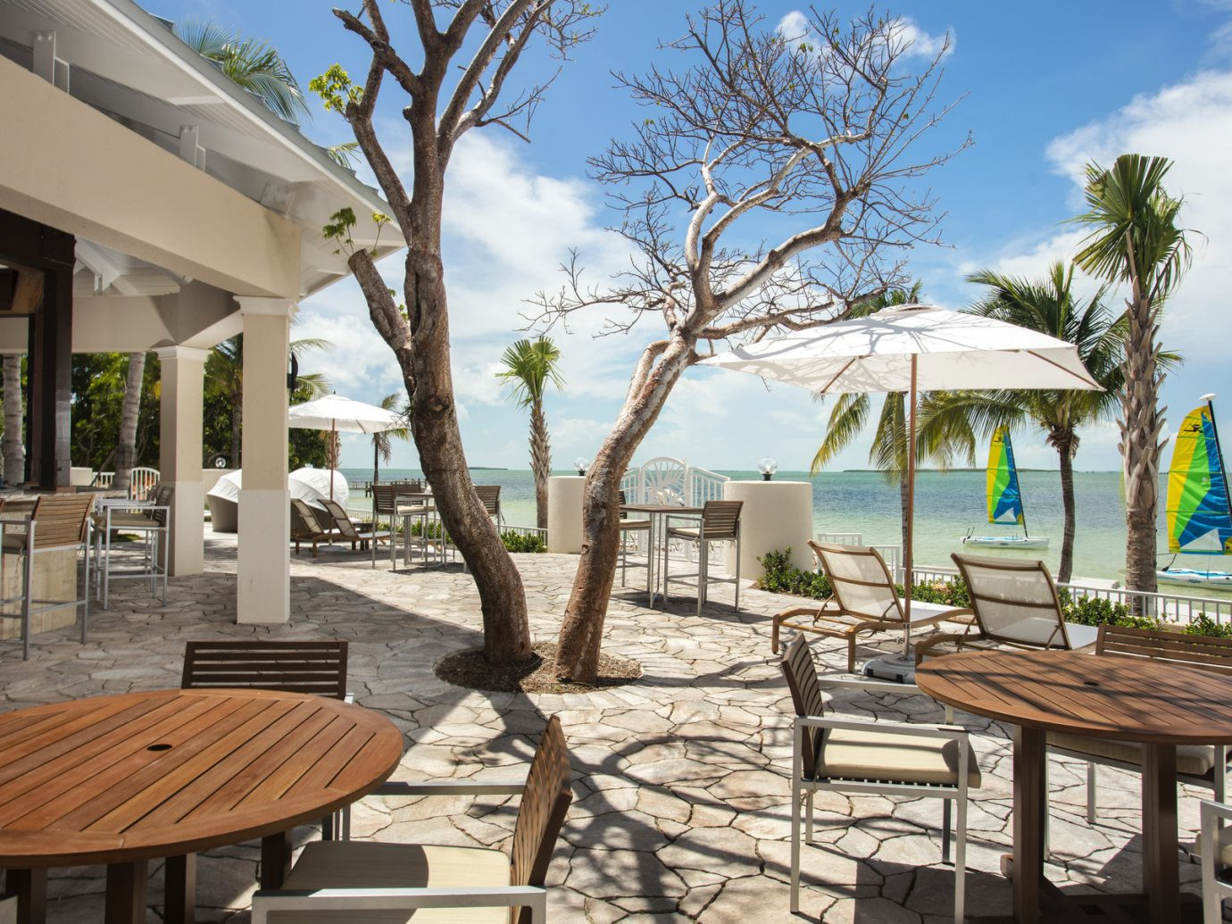 Hotels outdoor tree sky ground chair leisure property Resort estate vacation home real estate Villa Beach caribbean cottage backyard lawn porch Deck shade furniture day