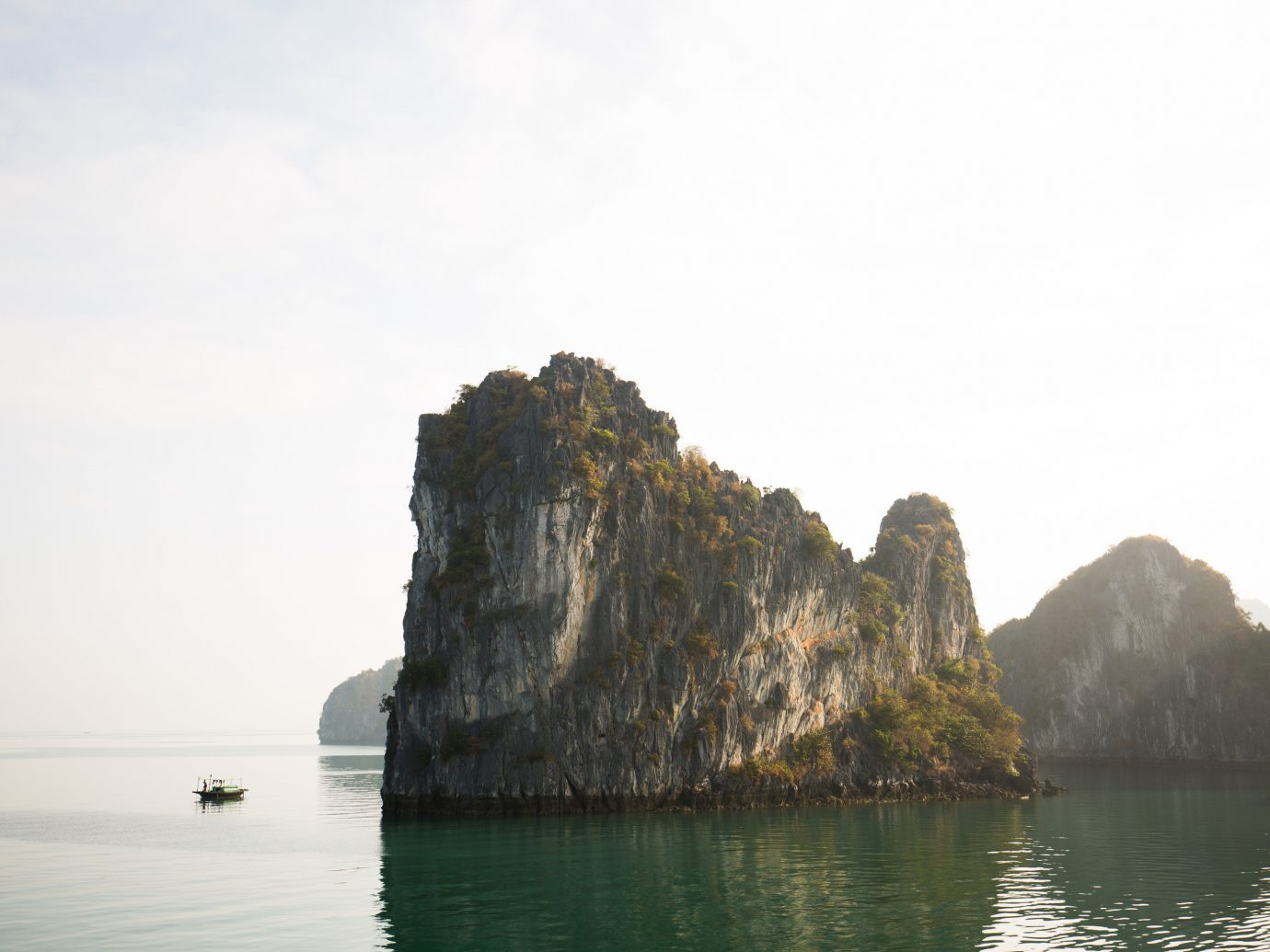 Offbeat water outdoor Boat landform Lake geographical feature Coast Sea body of water cliff rock Nature bay mountain shore Ocean terrain vehicle cape floating islet surrounded distance Island day