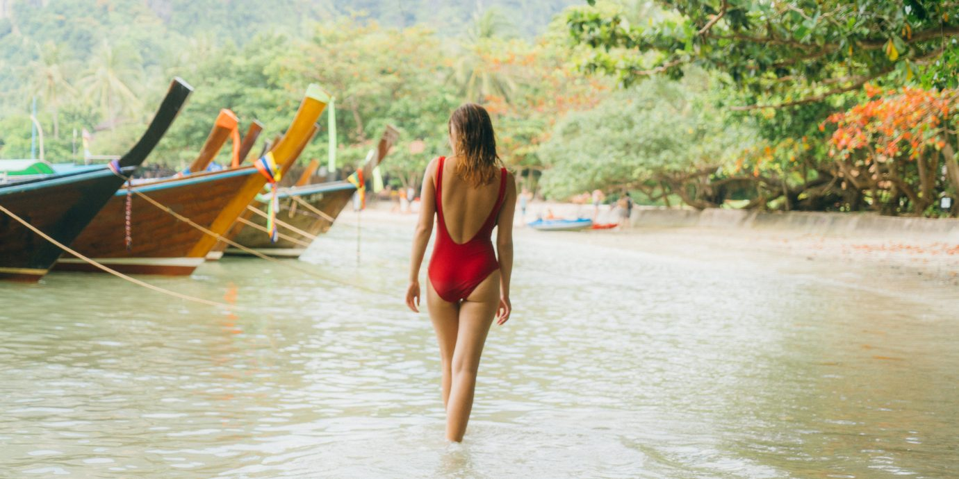 model wearing back plunge red one piece bathing suit