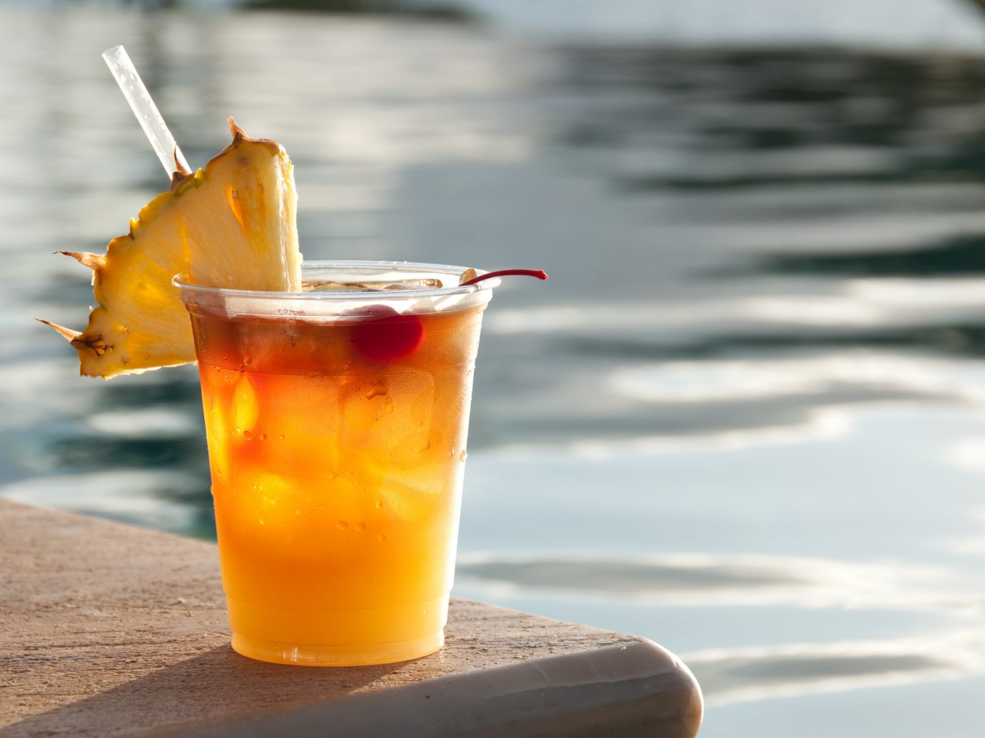 Mai Tai cocktail sitting on the edge of a swimming pool.