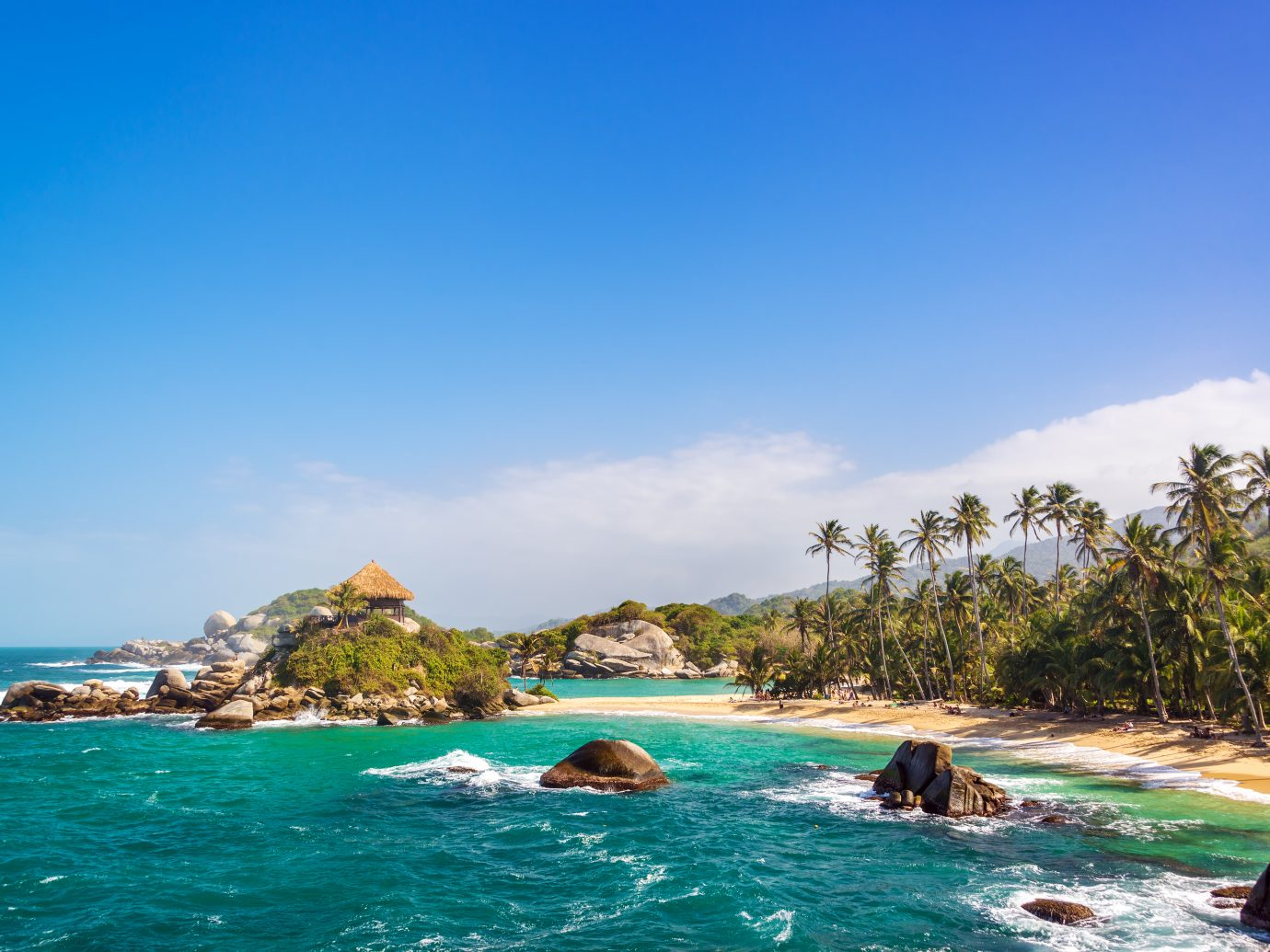 Palm trees and blue Caribbean water on the beach of San Juan del Guia in Tayrona National Park in Colombia