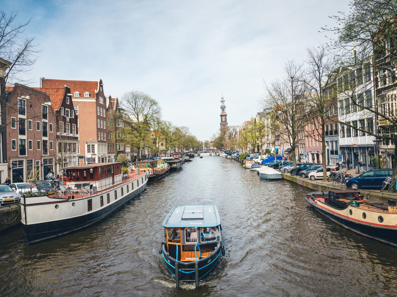 Amsterdam, Netherlands - April 17, 2018: Sightseeing boat cruising through the Prince's canal in Amsterdam. There is Westerkerk church visible in the background.