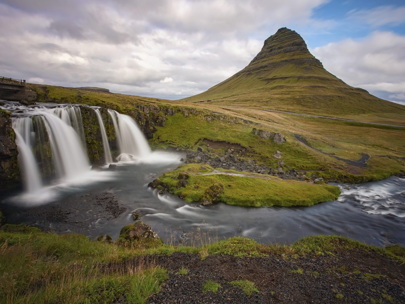 Kirkjufellsfoss mountain, located on the Snæfellsnes Peninsula of Iceland, with waterfalls in the foreground.
