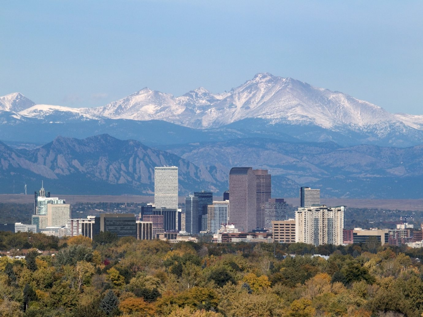 """With the snow covered Longs Peak part of the Rocky Mountains and the iconic flatirons of Boulder in the background, Downtown Denver skyscrapers including the iconic """"mailbox"""" or """"cash register"""" building as well as hotels, office buildings and apartment buildings fill the skyline."""