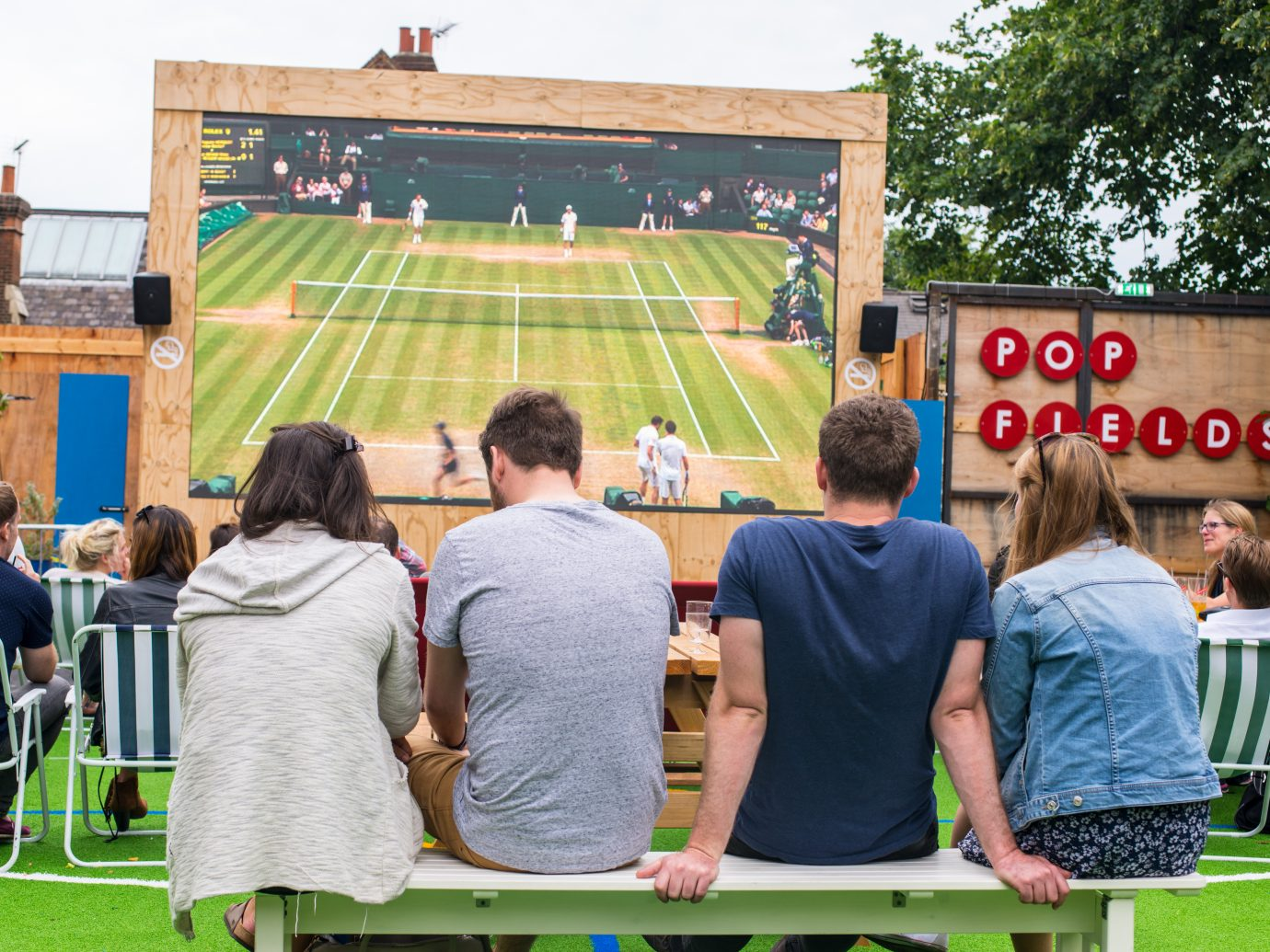 People talking and drinking while watching Wimbledon tennis match in a big outdoor screen in Pop Fields, part of the trendy venue Pop Brixton, South London.