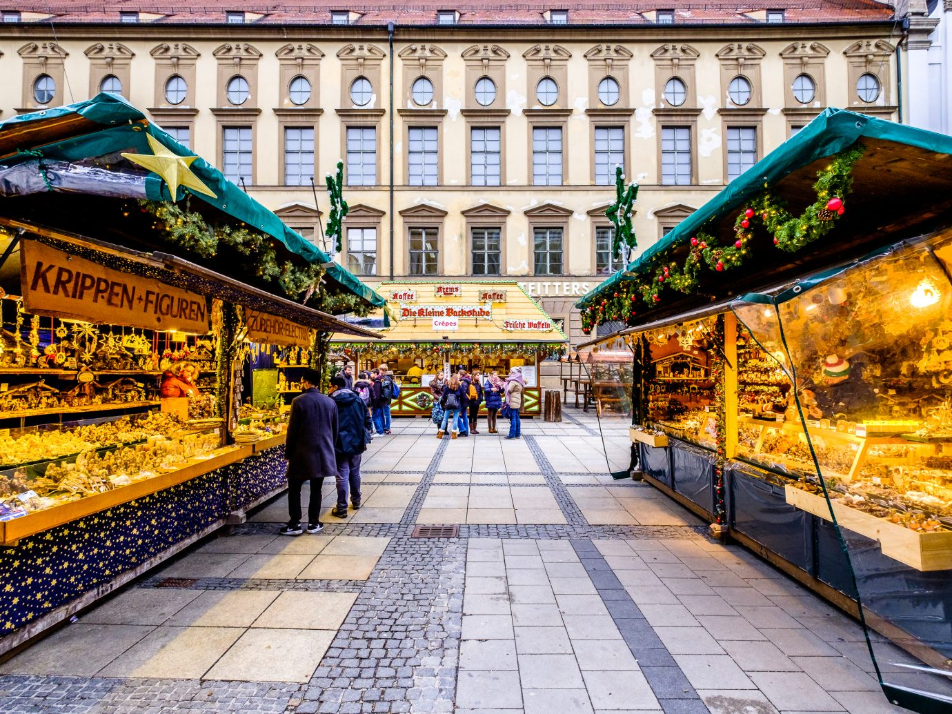 people and sales booth at the christmas market in Munich, Germany. the munich christmas market takes place annually on the marienplatz and the surrounding streets and is famous for its stalls selling arts and crafts. directly on the marienplatz the old city hall forms the background.